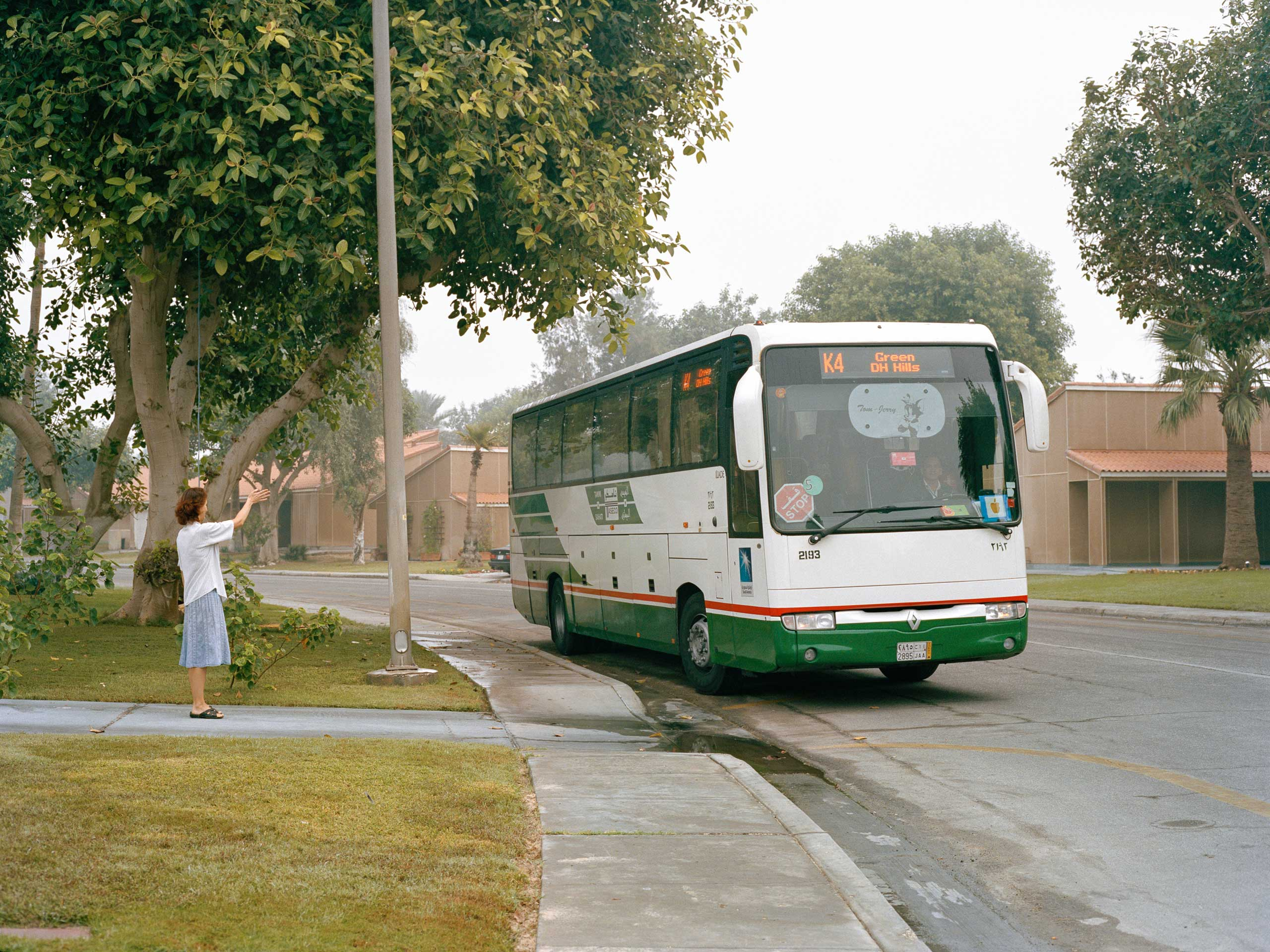 A mother waves goodbye to her daughter on Lemon Circle as she leaves for Dhahran School on the school bus at 7am. Aramco schools are all located within the compound.