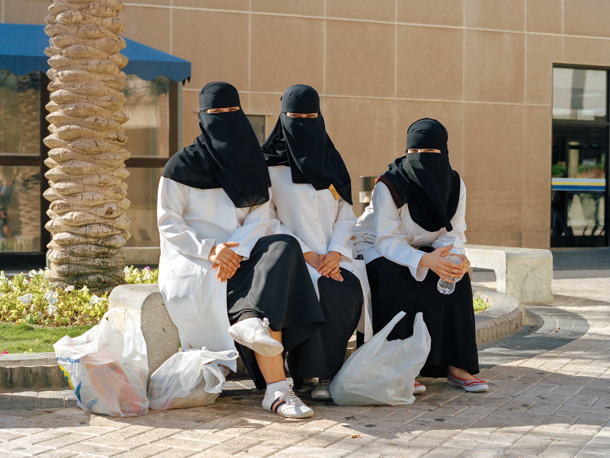Nurses from Dhahran Health Center wait for a bus after work in front of the Commissary. Saudi Aramco's health center was first operated by the company itself, but since 2014, it became Johns Hopkins Aramco Healthcare, the first-of-its-kind health care joint venture between Saudi Aramco, a world leader in energy, and Johns Hopkins Medicine.