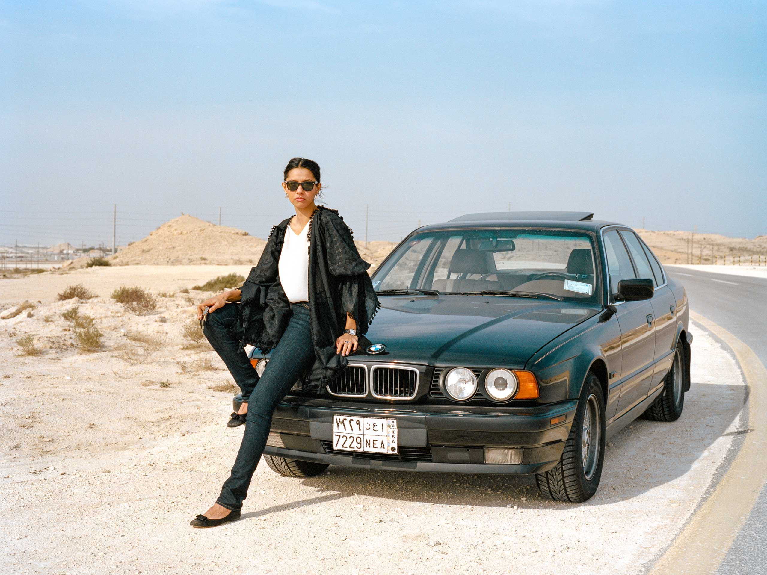 Sahrr sits on her car after driving out to the jebels on the Western side of Dhahran. In Arabic, jebel means mountain or hill. Many Aramcons use the term to refer to large rocky areas. While women are not allowed to drive in Saudi Arabia, they are allowed to drive within Aramco compounds, including Dhahran, the largest of them all.