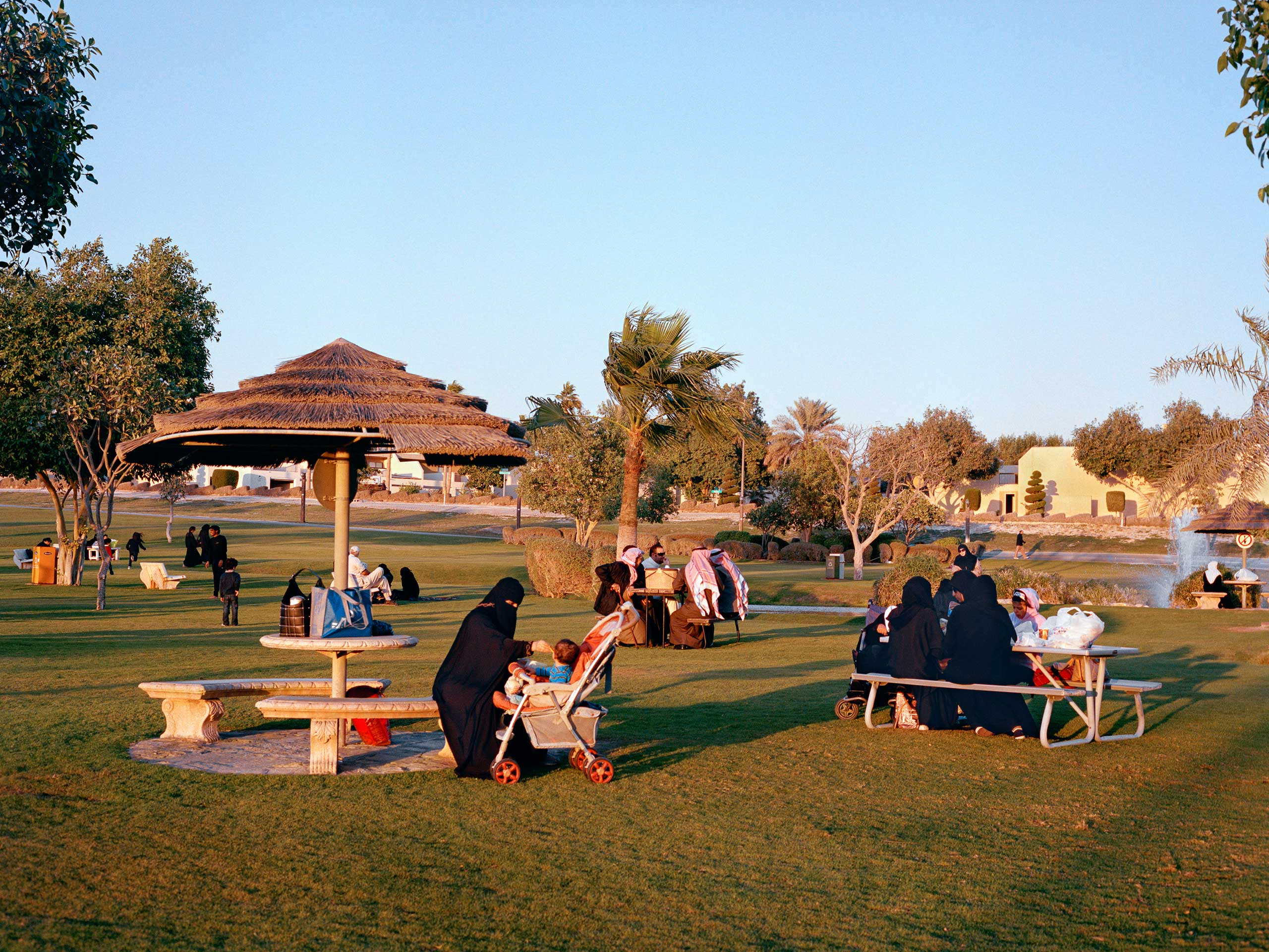 "Families relax by ""The Pond"" at sunset. ""The Pond"" is on the North East corner of the Dhahran Golf Course in Dhahran, Saudi Arabia."