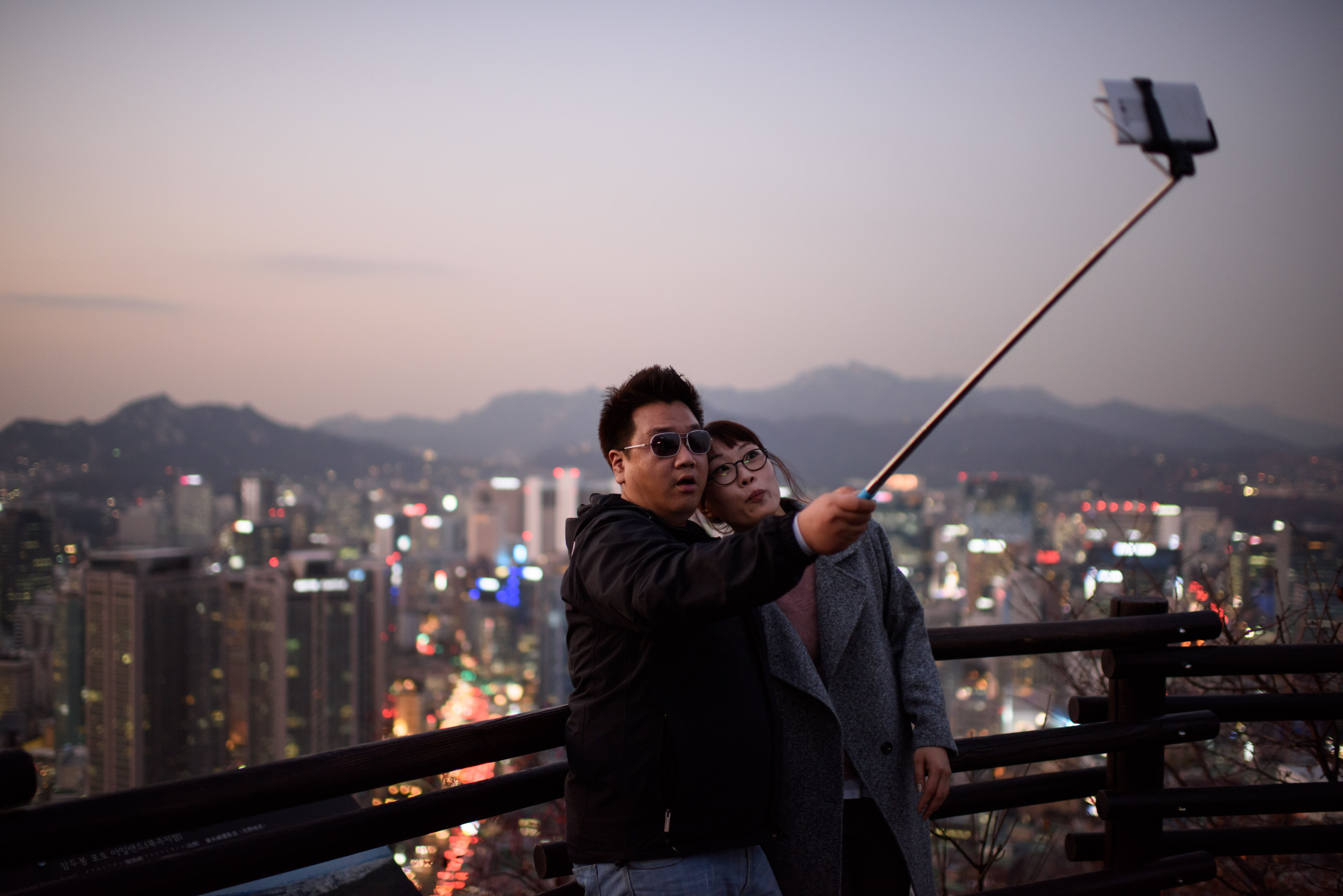A couple use a 'selfie stick' to take a photo overlooking the city skyline of central Seoul on Nov. 26, 2014.