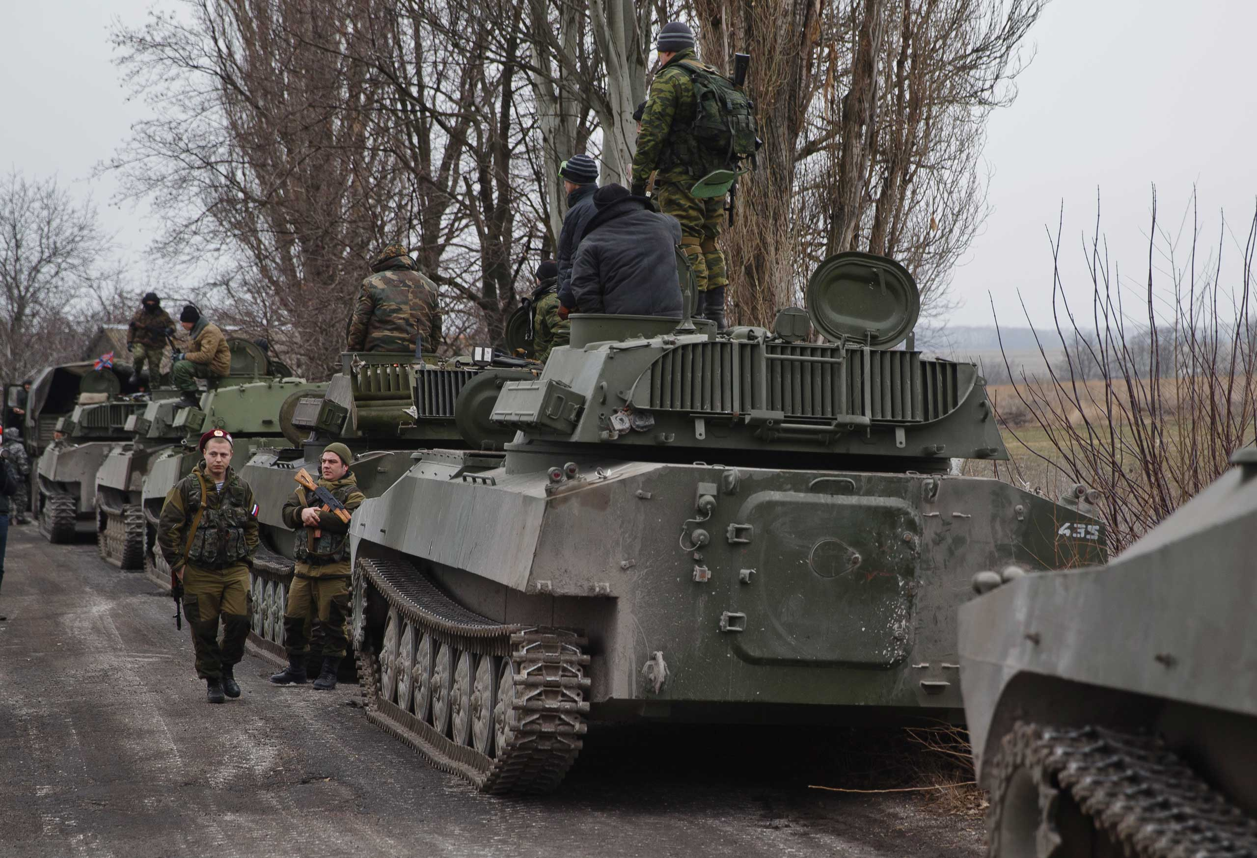 Russia-backed separatist fighters stand next to self propelled 152 mm artillery pieces, part of a unit moved away from the front lines, in Yelenovka, near Donetsk, Ukraine, Feb. 26, 2015.