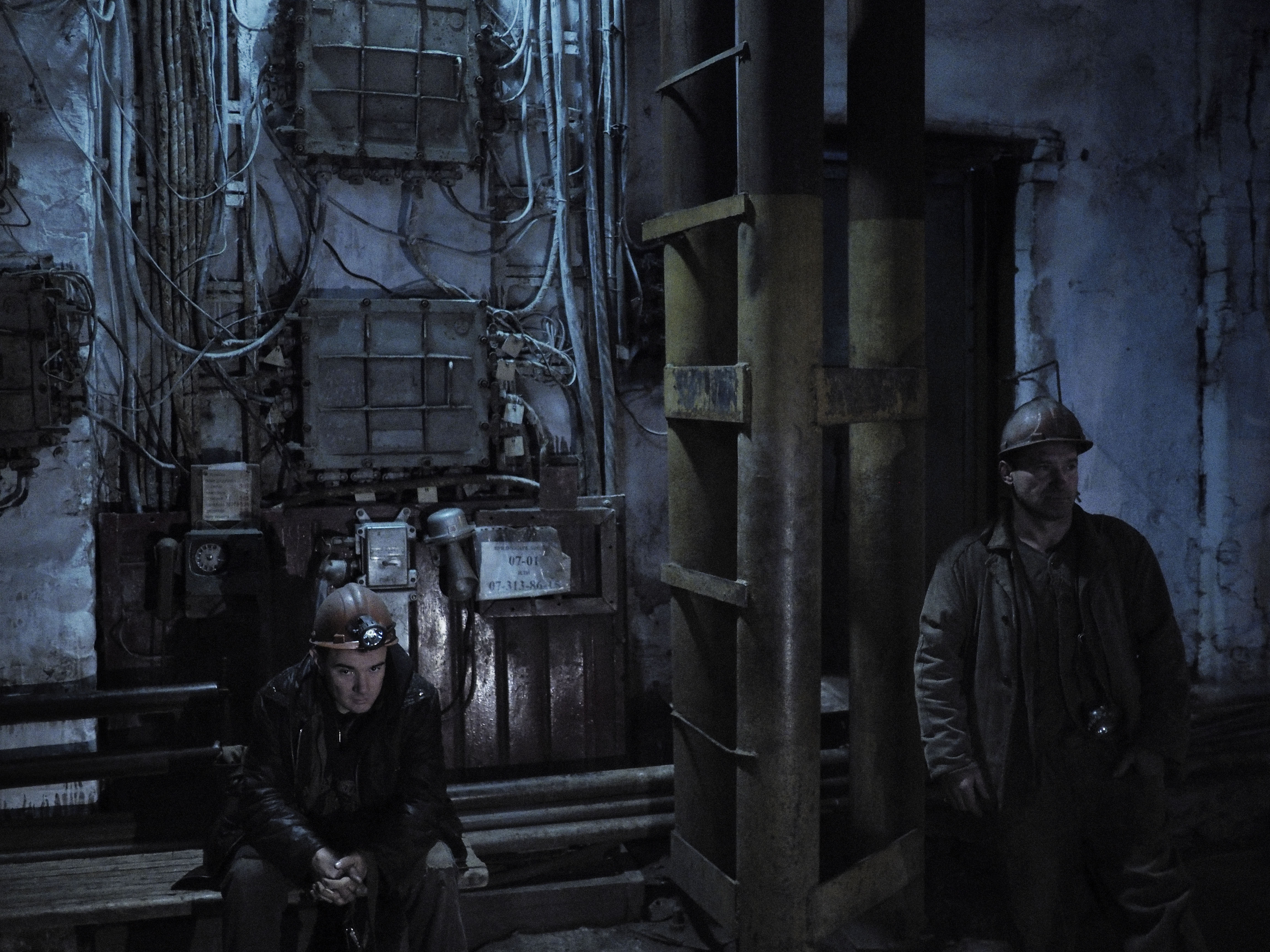 Two miners at the Chelyuskintsev coal mine wait for an elevator that will take them to the bottom of the deepest shaft. They are still operating despite the mine enduring constant shelling from Ukrainian army artillery, besieging the city. Petrovskyi district, Donetsk, Ukraine. Nov. 28, 2014.From  Beneath the Front Lines of the War in Eastern Ukraine