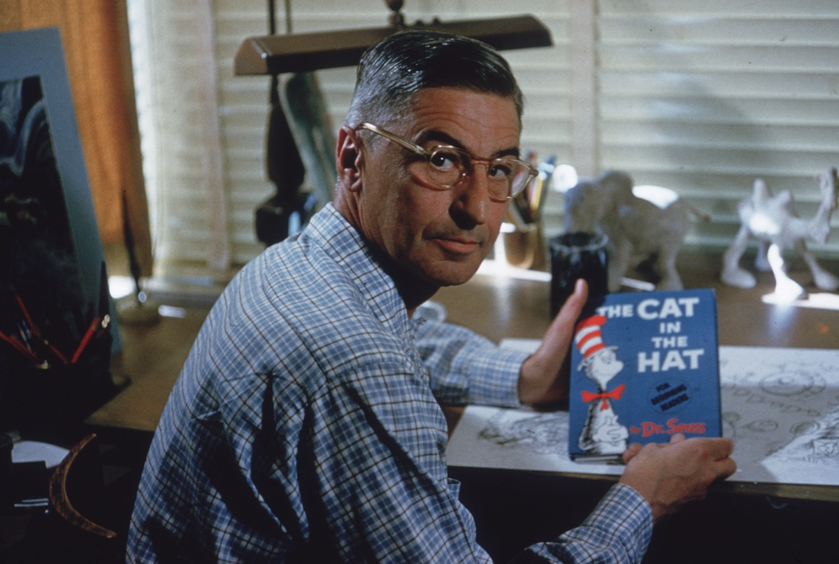 Dr Seuss sits at his drafting table in his home office with a copy of his book, 'The Cat in the Hat', La Jolla, Calif., Apr. 25, 1957.