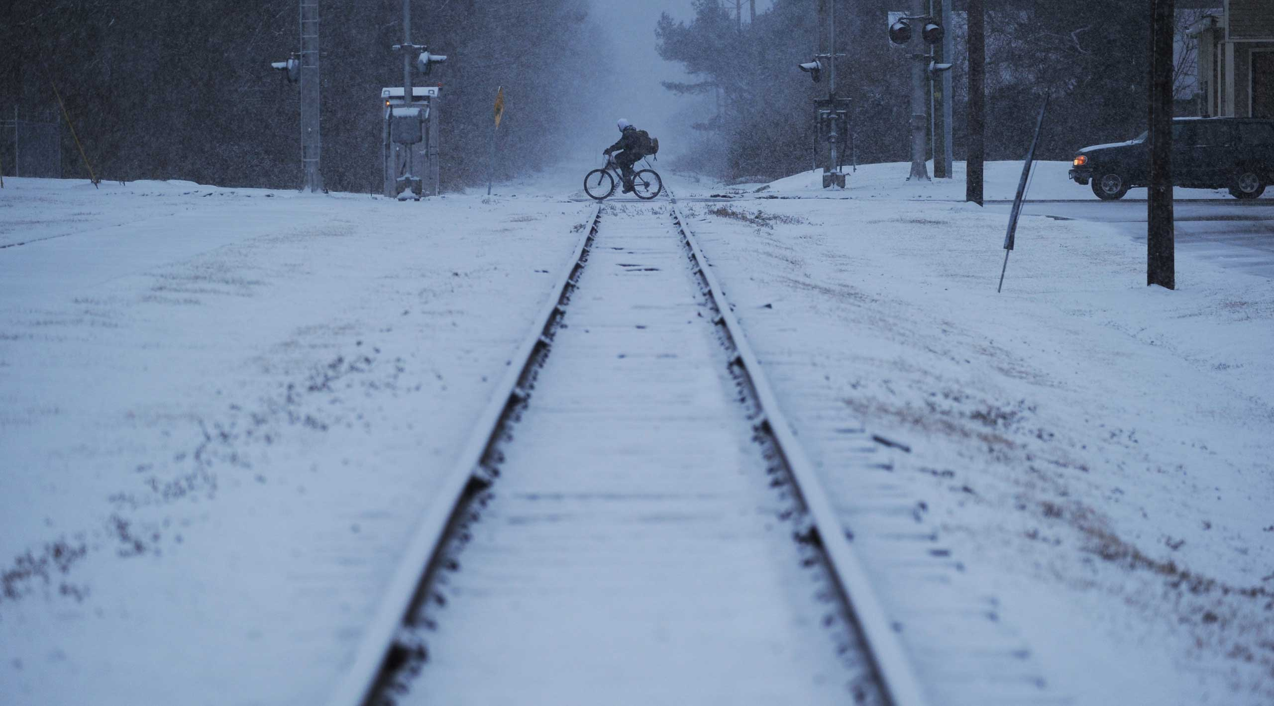A man rides his bicycle across the railroad tracks in Exmore, Va. as snow falls, Feb. 24, 2015.