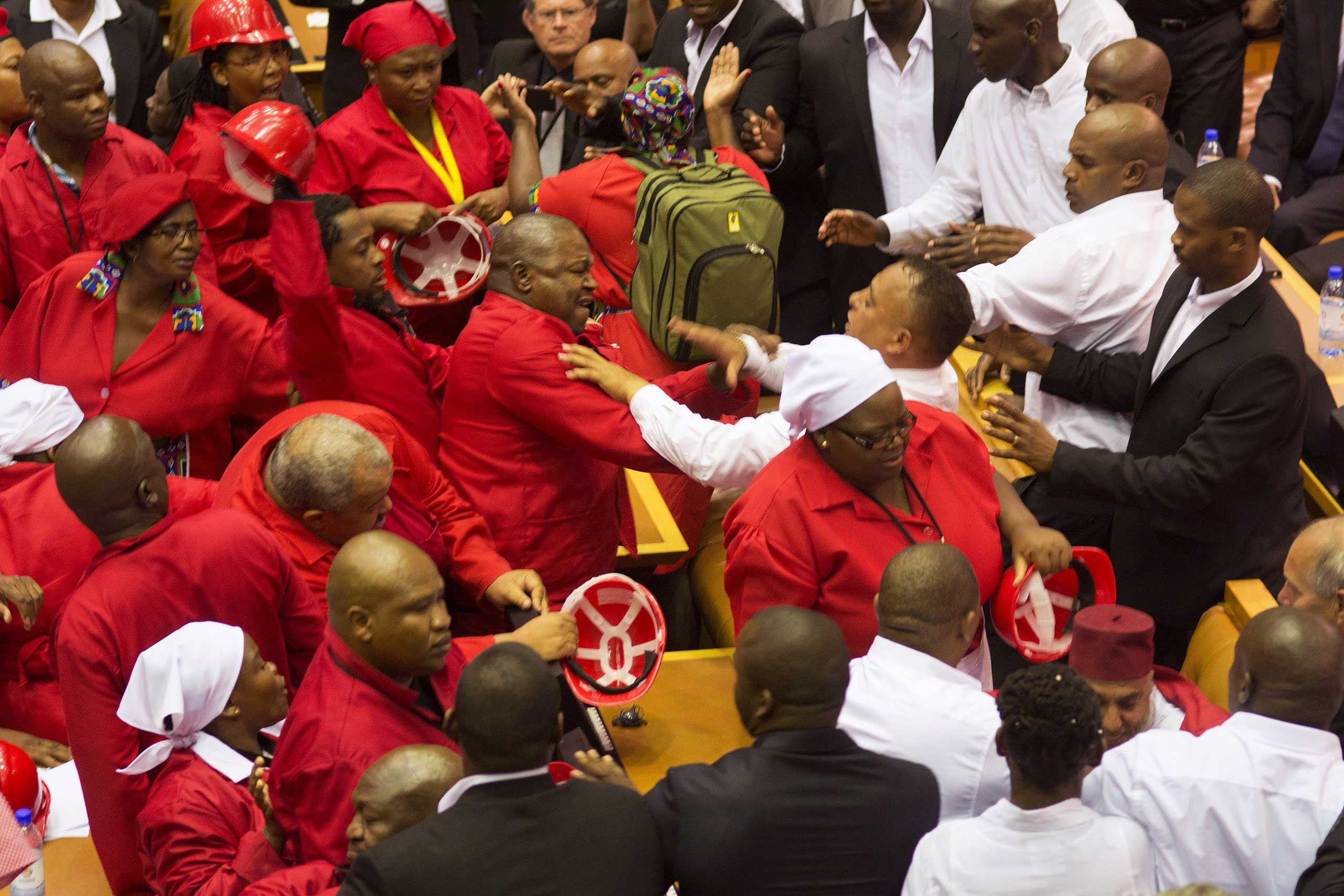 Members of the Economic Freedom Fighters, wearing red uniforms, clash with security forces during South African President's State of the Nation address in Cape Town on Feb. 12, 2015.