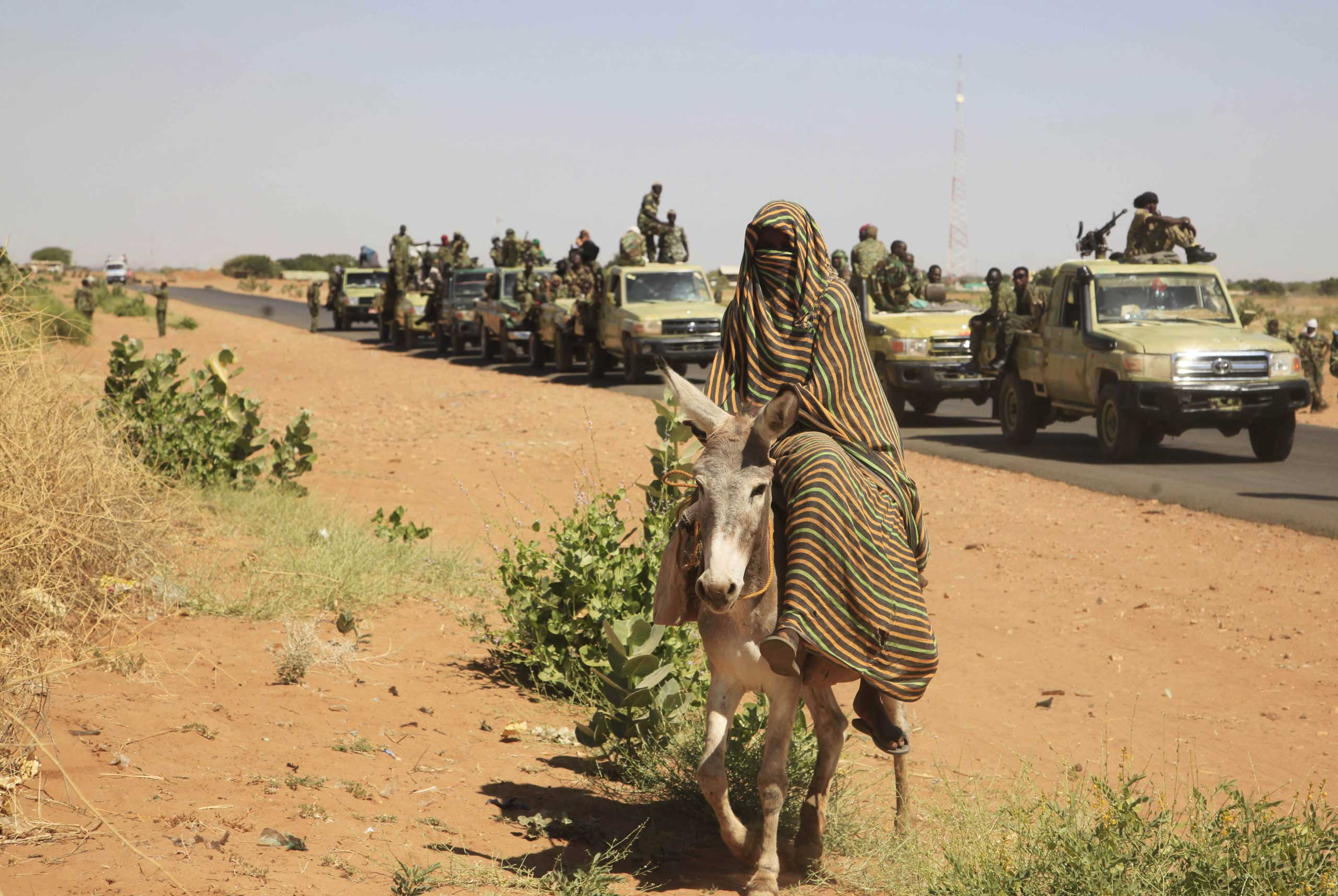 A woman rides a donkey past a convoy of government troops in Tabit village in the North Darfur region of Sudan, Nov, 2014.