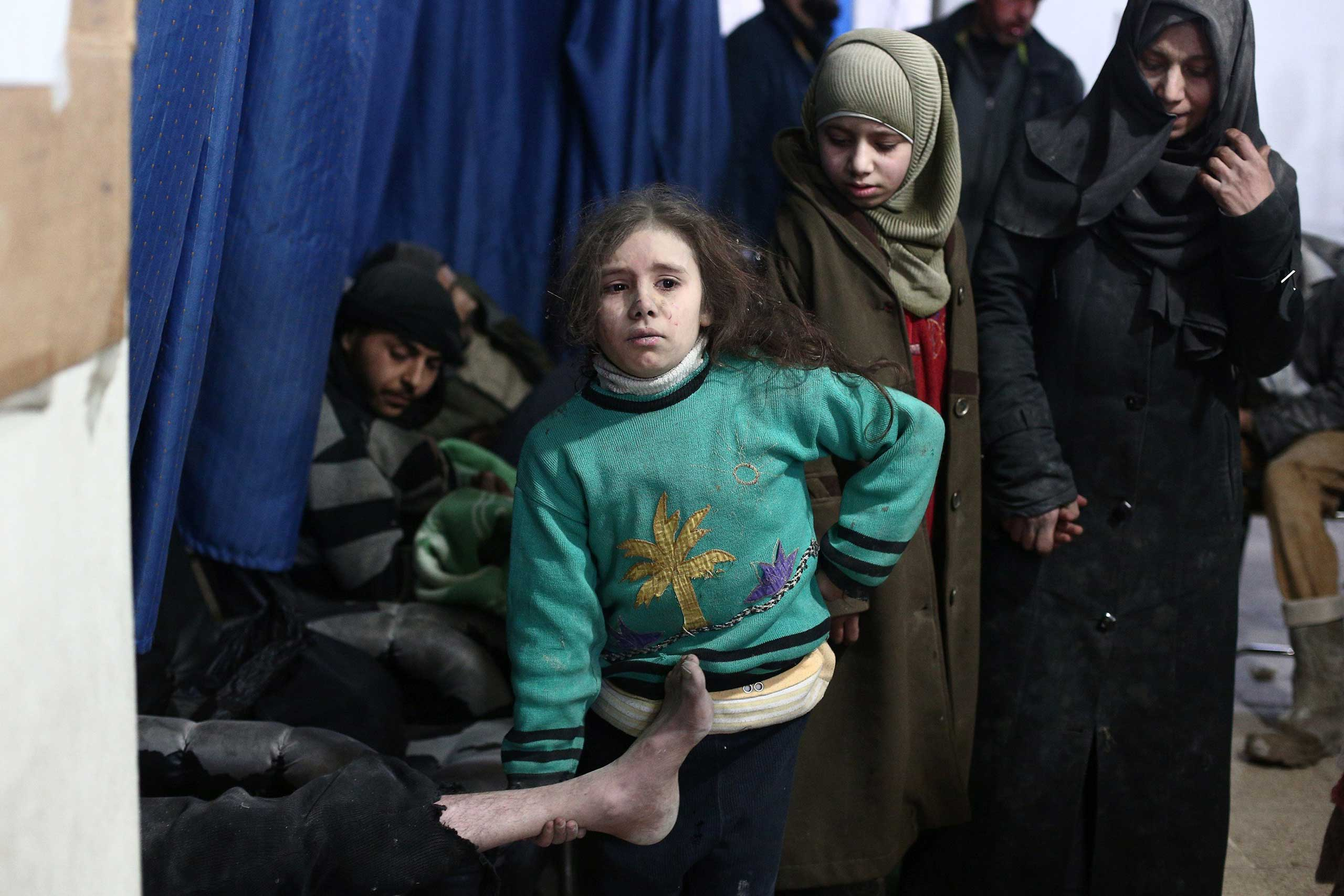 A Syrian girl holds the leg of her injured father as they wait for treatment at a clinic in in the Douma neighborhood of Damascus, following reported air strikes by regime forces on Feb. 9, 2015.