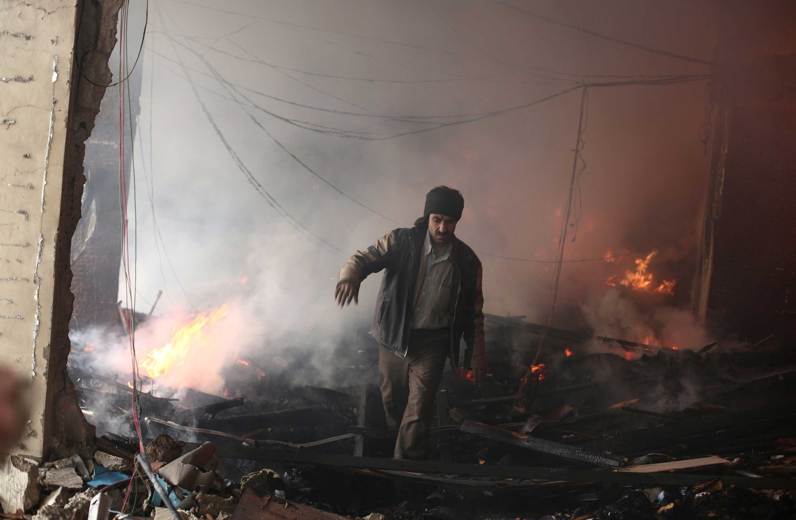 A Syrian man walks amid debris inside a heavily damaged building following reported air strikes by regime forces in the Douma neighborhood of Damascus, on Feb. 9, 2015.