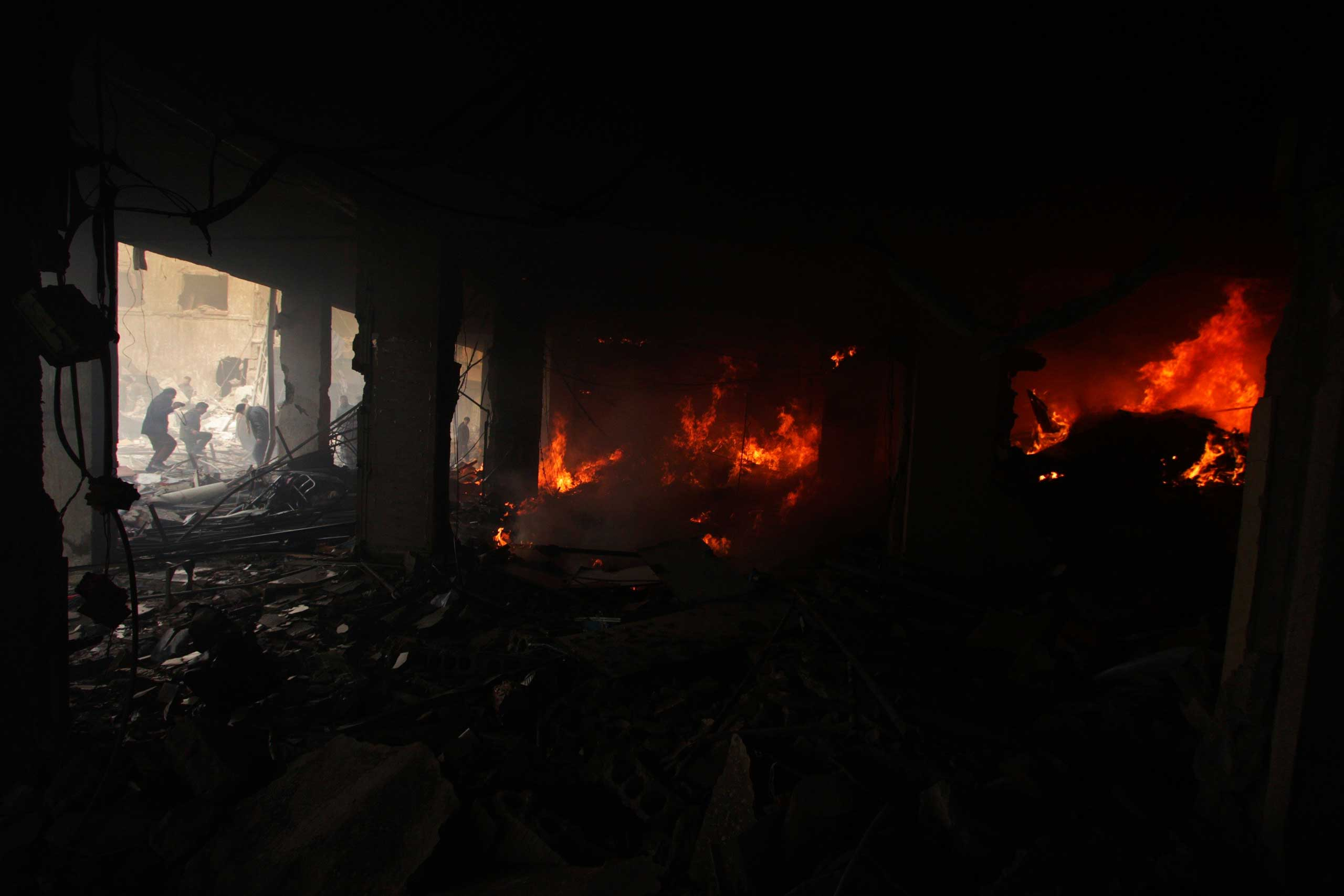 People try to put out a fire after what activists said were airstrikes followed by shelling by forces loyal to Syria's President Bashar Assad in the Douma neighborhood of Damascus, Feb, 9, 2015.