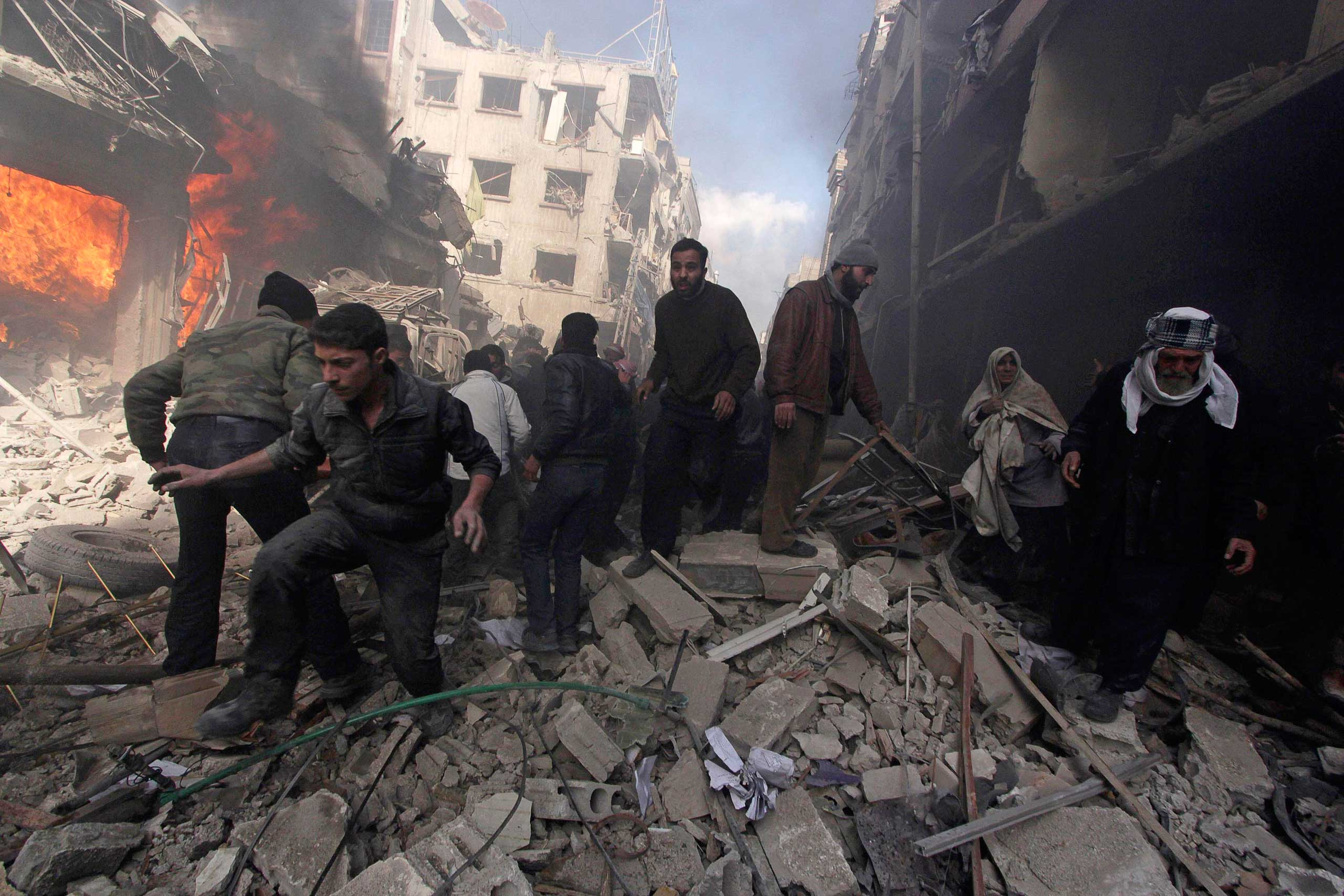 People walk on rubble as others try to put out a fire after what activists said were airstrikes followed by shelling by forces loyal to Syria's President Bashar Assad in the Douma neighborhood of Damascus, Feb. 9, 2015.