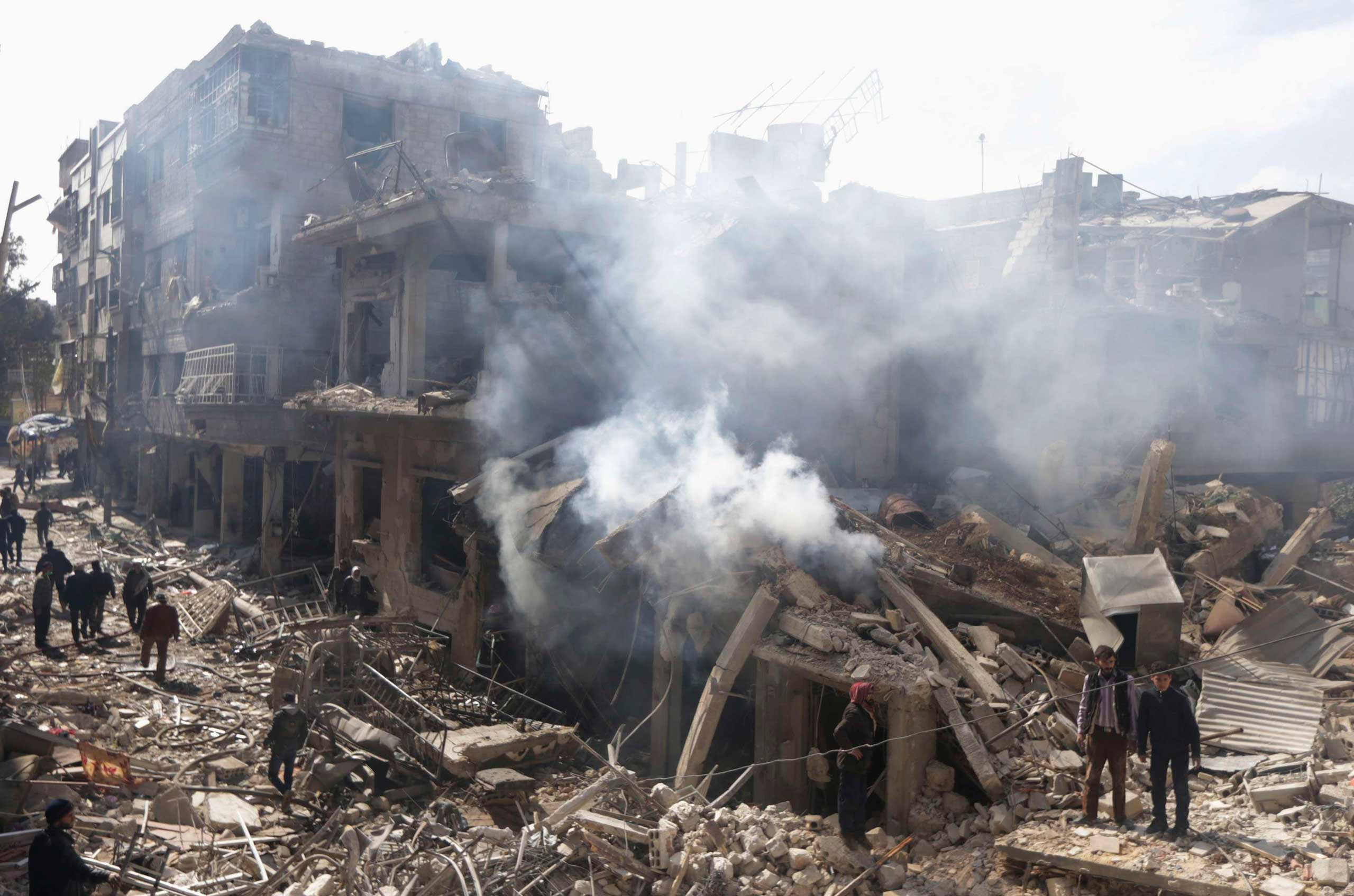 People inspect a site hit by what activists said were airstrikes by forces loyal to Syria's President Bashar Assad in the Douma neighborhood of Damascus, Feb. 9, 2015.