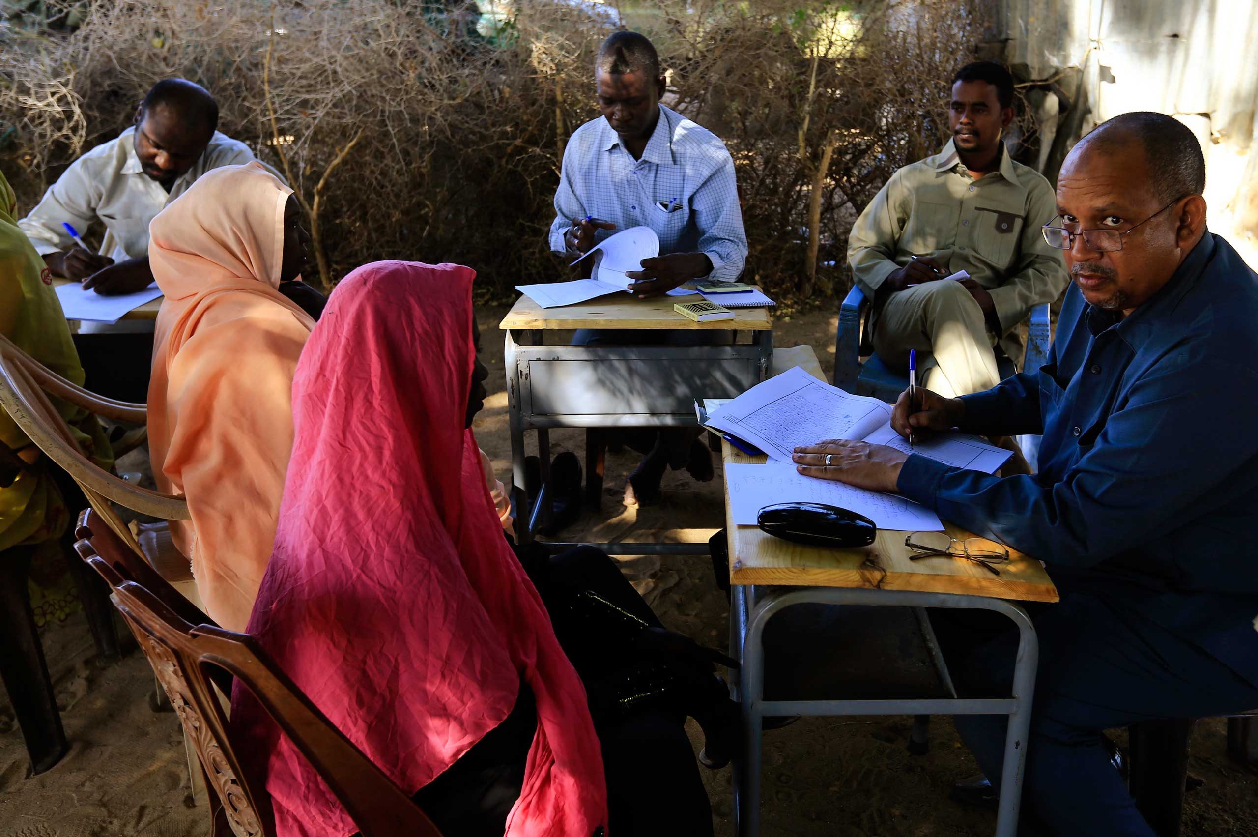 Special Prosecutor for Crimes in Darfur Yasir Ahmed Mohamed and his team talk to women during an investigation into allegations of mass rape in the village of Tabit, in North Darfur, Nov. 20, 2014.