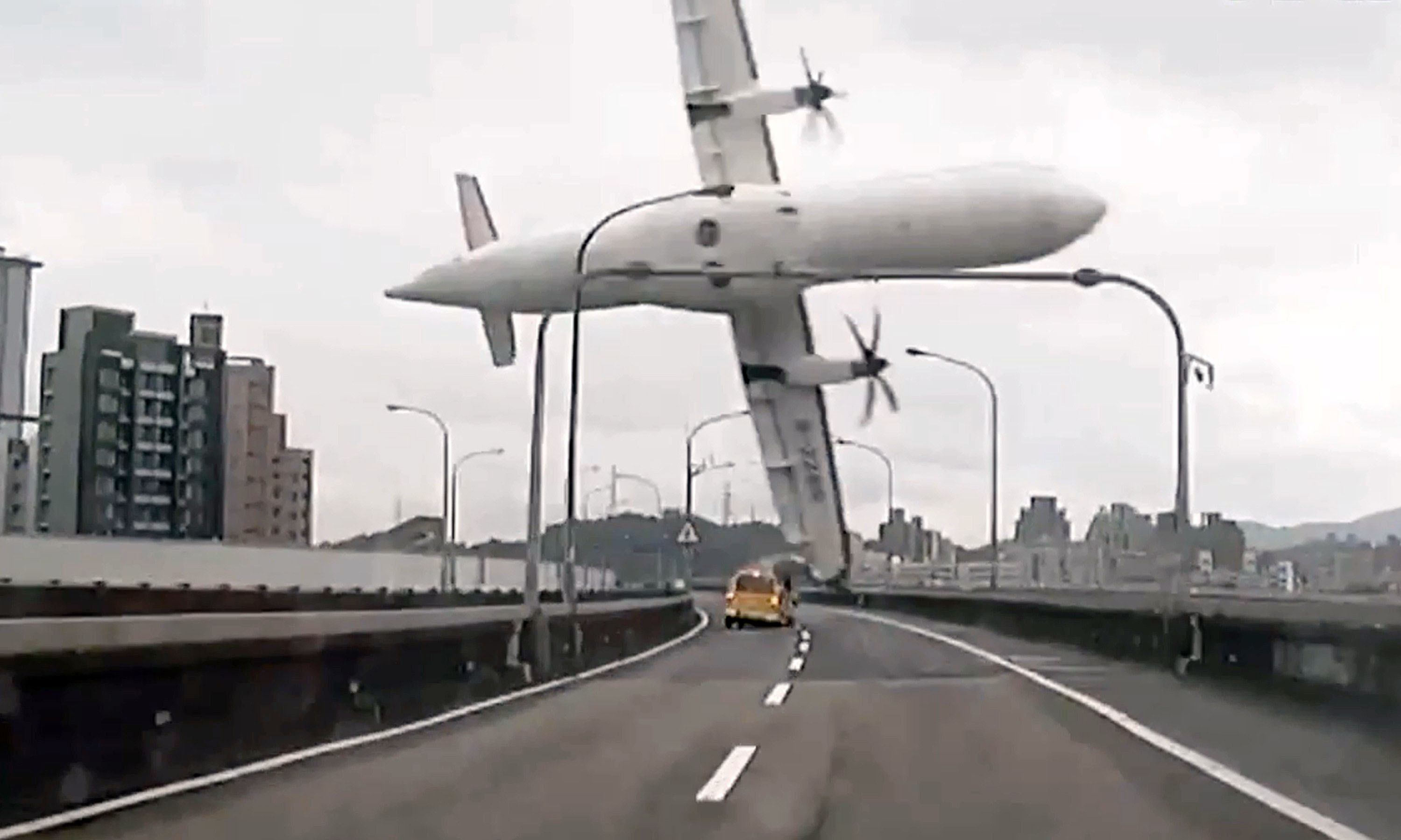 This screen grab taken from a video shows a TransAsia ATR 72-600 turboprop plane clipping an elevated motorway and hitting a taxi (C) before crashing into the Keelung river outside Taiwan's capital Taipei in New Taipei City on Feb.  4, 2015.