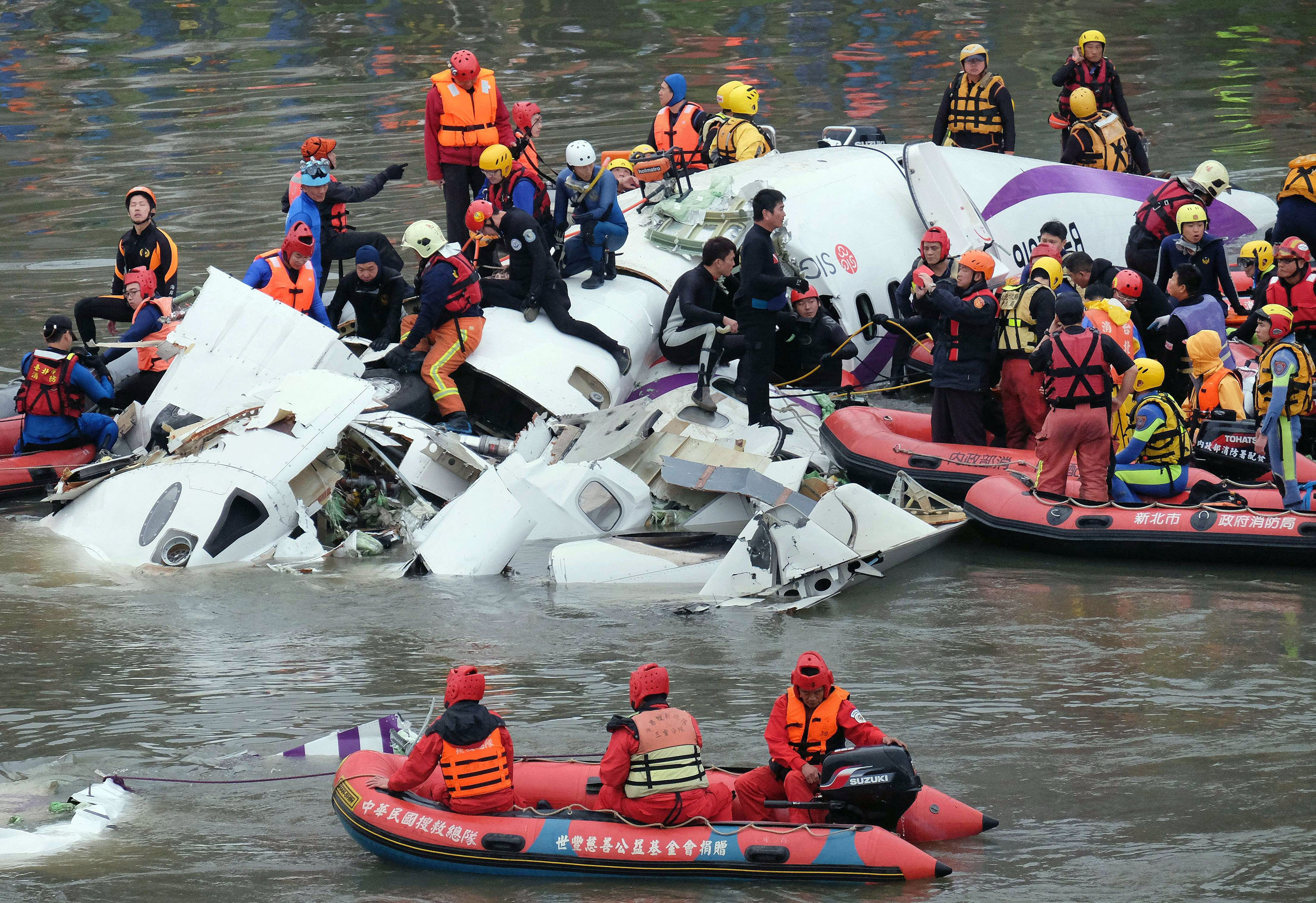 Rescue personnel search for passengers from the wreckage of a TransAsia ATR 72-600 turboprop plane that crash-landed into the Keelung river outside Taiwan's capital Taipei in New Taipei City on Feb.  4, 2015.