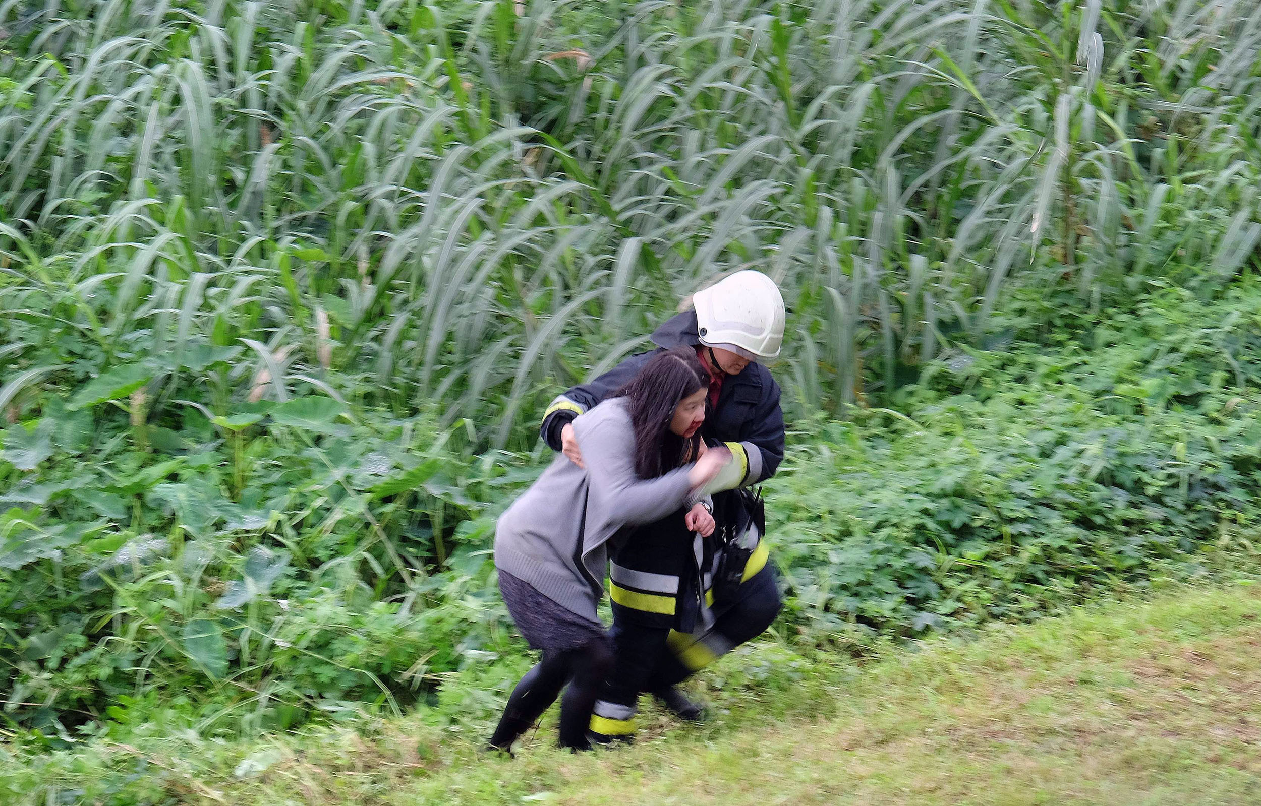 An injured passenger (L) is escorted by emergency personnel up the river bank after a TransAsia ATR 72-600 turboprop plane crash-landed into the Keelung river outside Taiwan's capital Taipei in New Taipei City on Feb. 4, 2015.