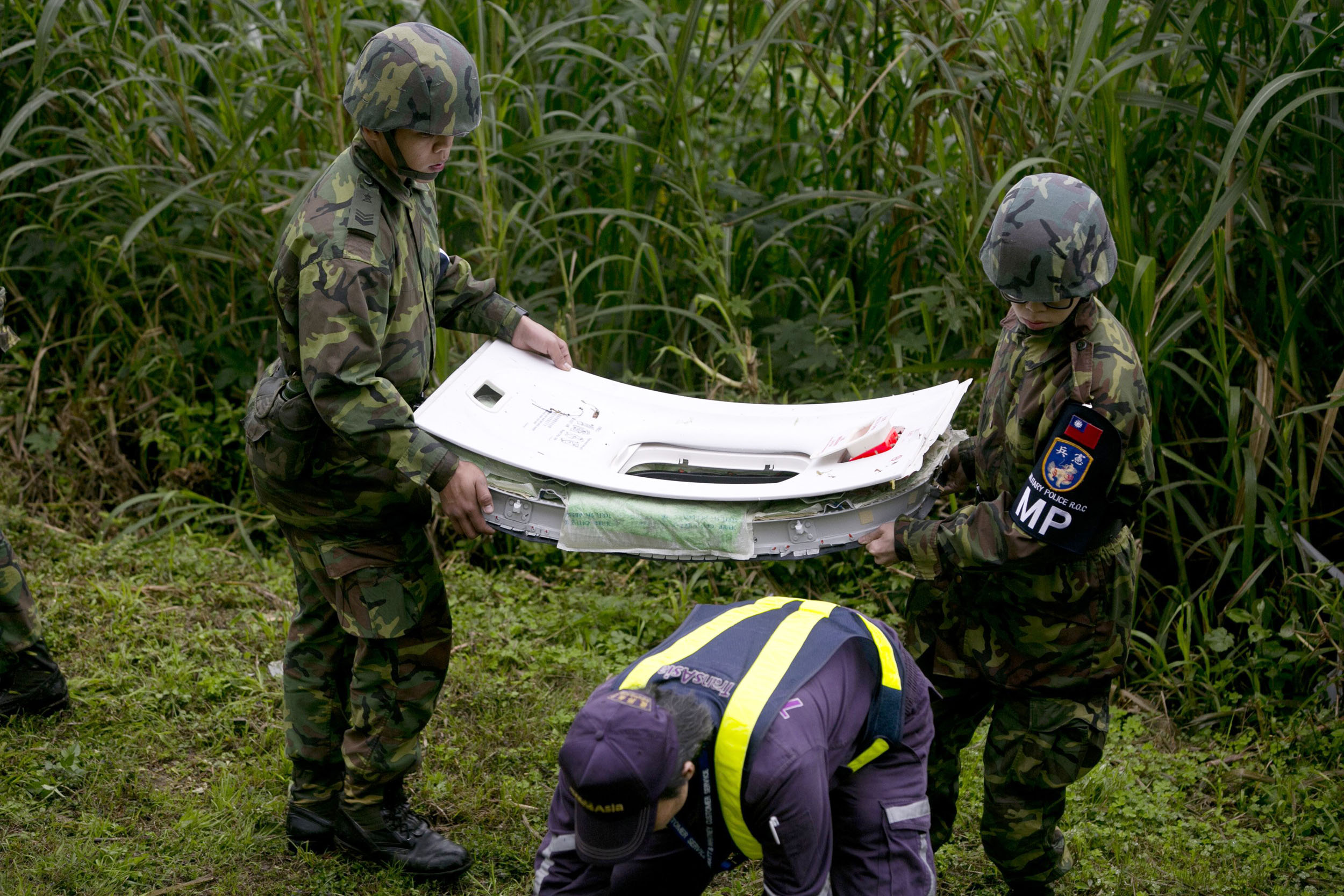 Rescue teams carrry a window from a TransAsia Airways ATR 72-600 turboprop airplane that crashed into the Keelung River shortly after takeoff from Taipei Songshan airport in Taipei, Taiwan on Feb. 4, 2015.