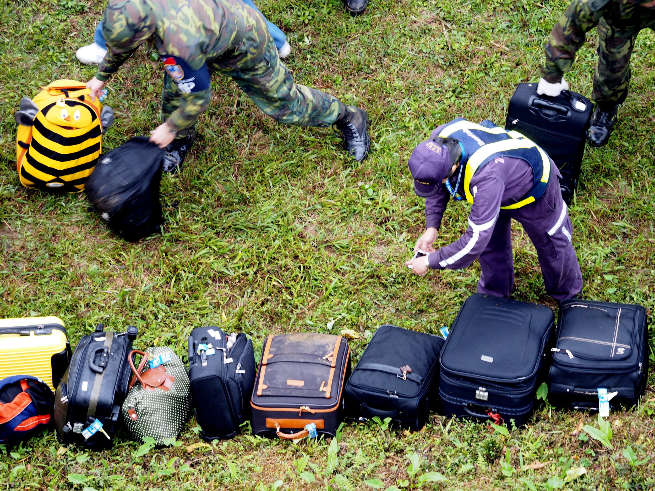A policeman takes photos of passengers' luggage recovered from a TransAsia Airways passenger plane which crashed into the Keelung River in Taipei, Taiwan on Feb. 4, 2015.