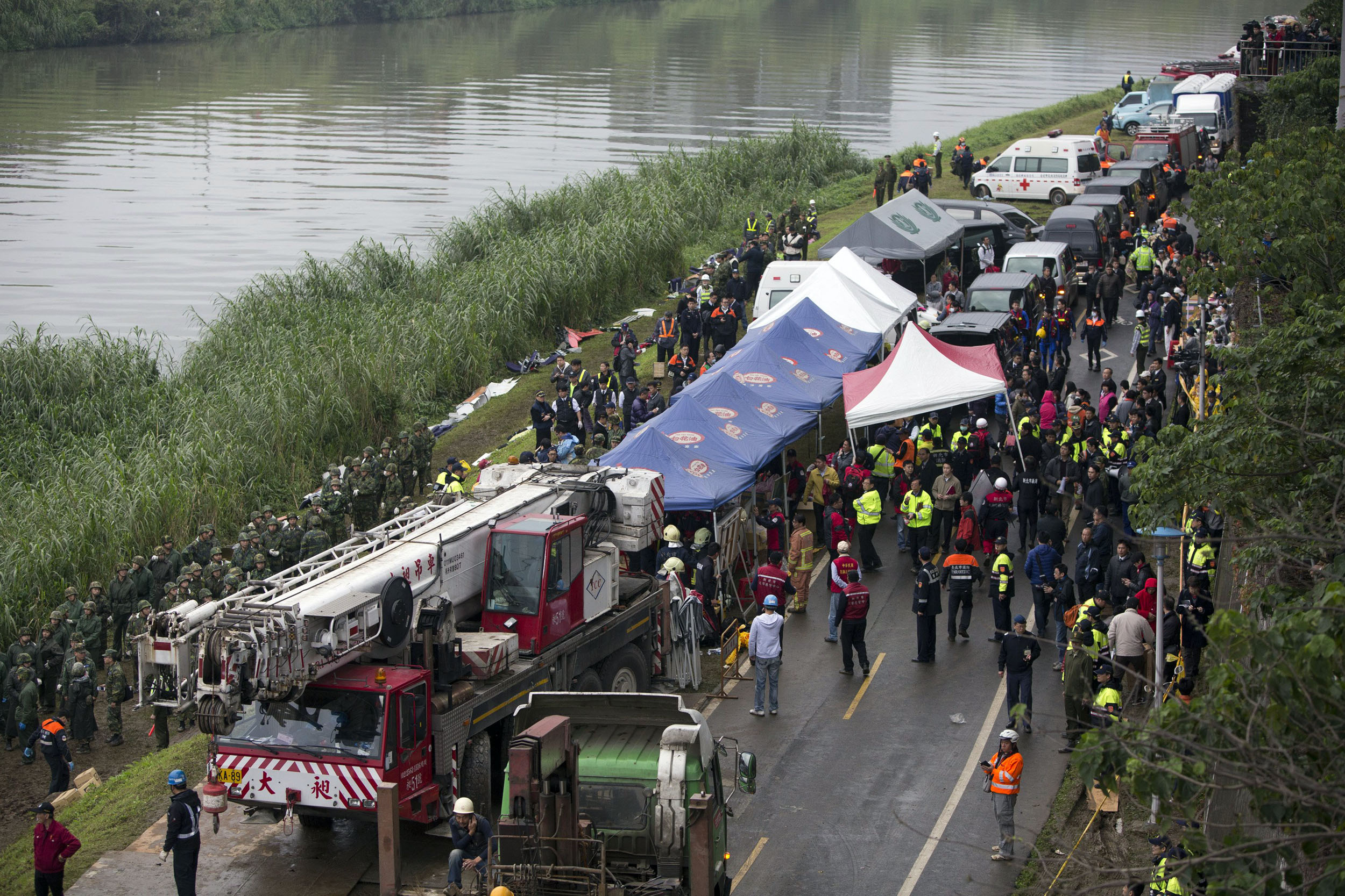 Rescue personnel, military and members of the media line up along the shore as rescue operations continue to free passengers from a TransAsia ATR 72-600 turboprop plane (not pictured) that crash-landed into a river (at L) outside Taiwan's capital Taipei in New Taipei City on Feb. 4, 2015.