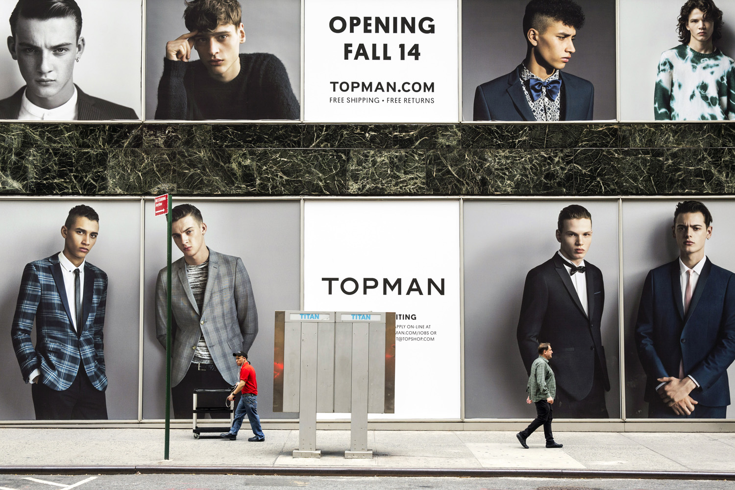 Two men pass by a billboard covering a new Top Shop flagship store on Fifth Avenue, New York, Apr 15, 2014.