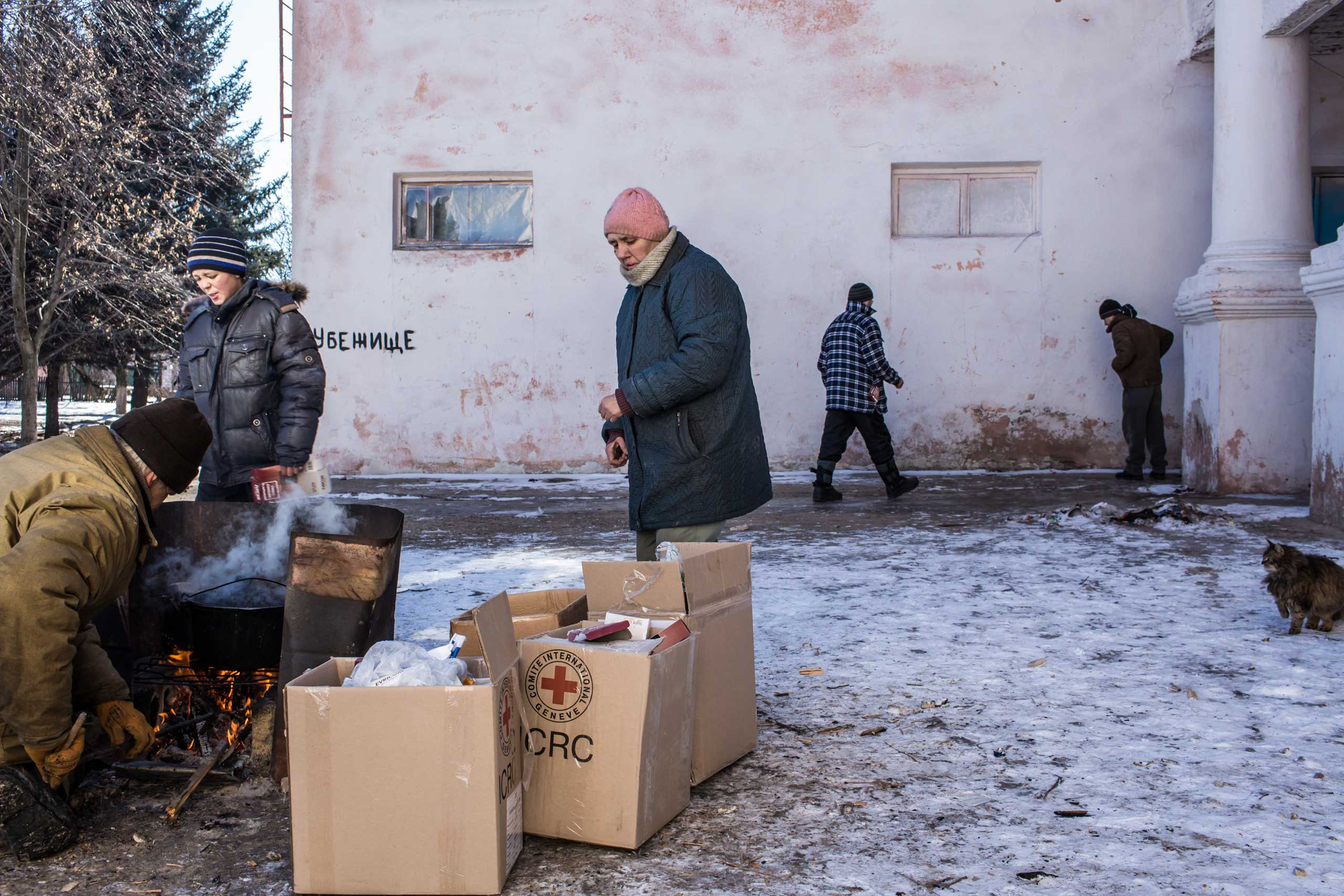 People cook lunch over a fire outside the local House of Culture, which serves as a distribution point for humanitarian aid and provides a bomb shelter, on Feb. 17, 2015 in Mironovka.