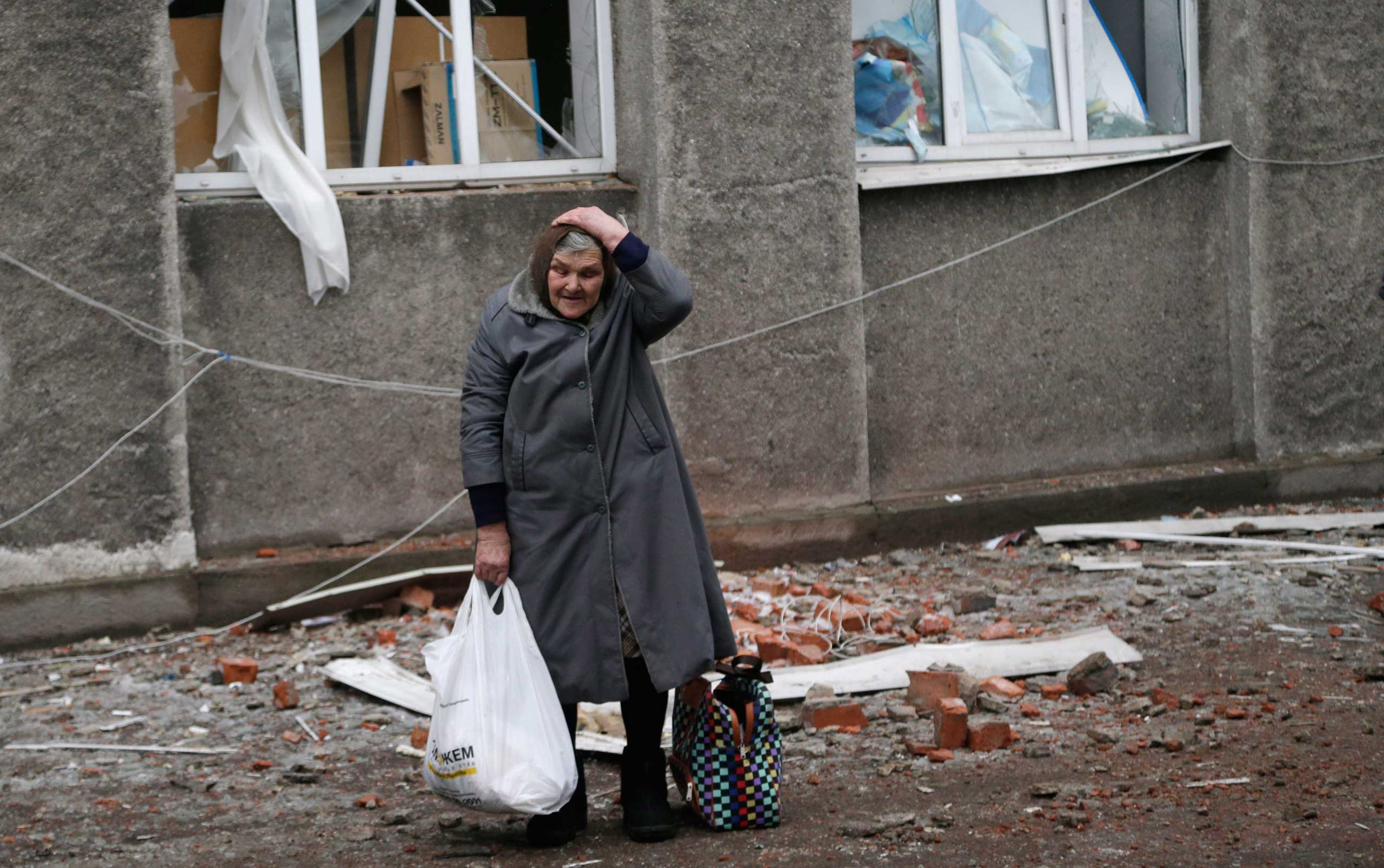 An elderly woman holds her head after collecting supplies of humanitarian aid in the town of Debaltseve, Ukraine,  Feb. 6, 2015.