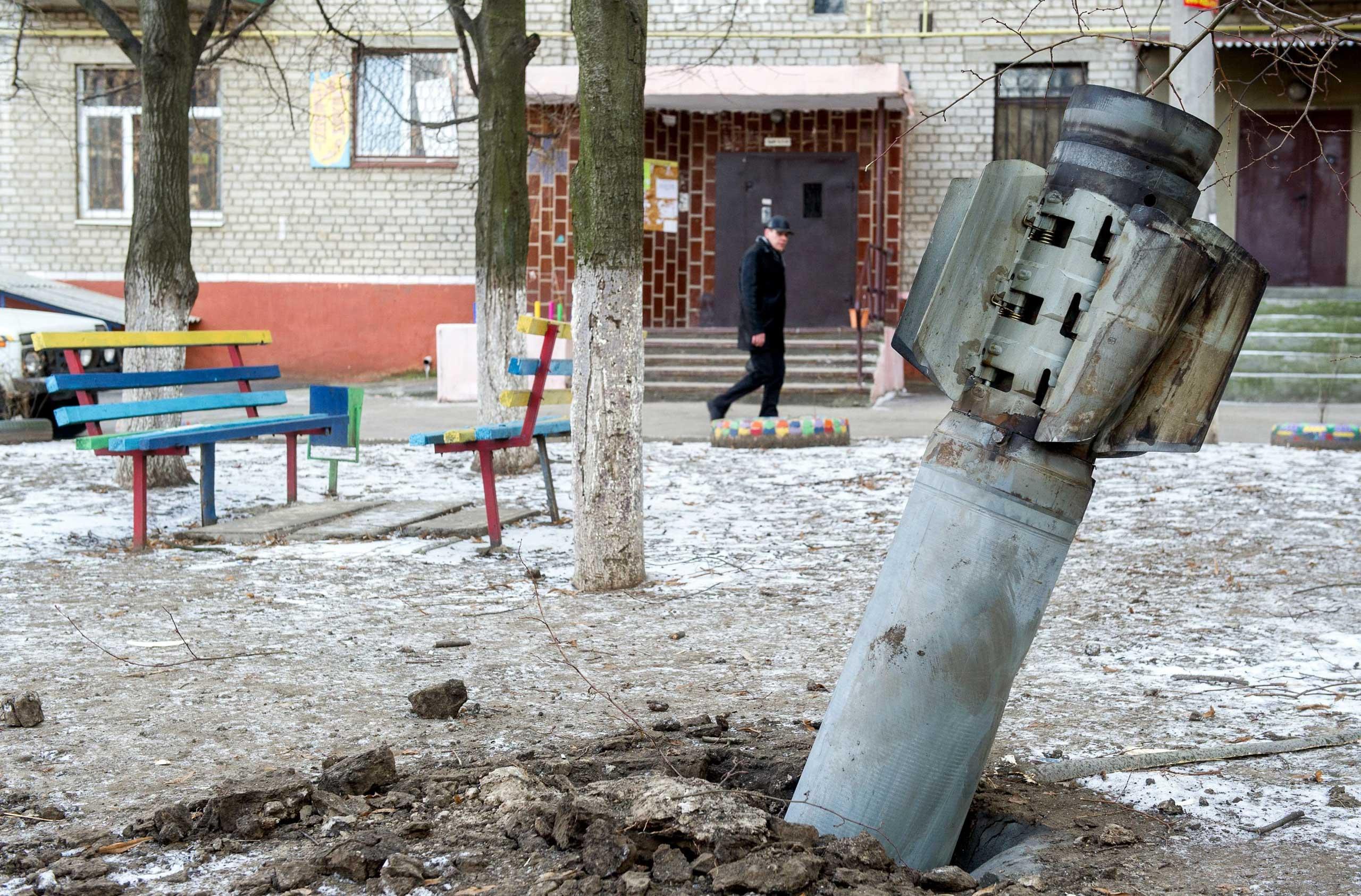 A man walks past an unexploded rocket in Kramatorsk, eastern Ukraine on Feb. 11, 2015.