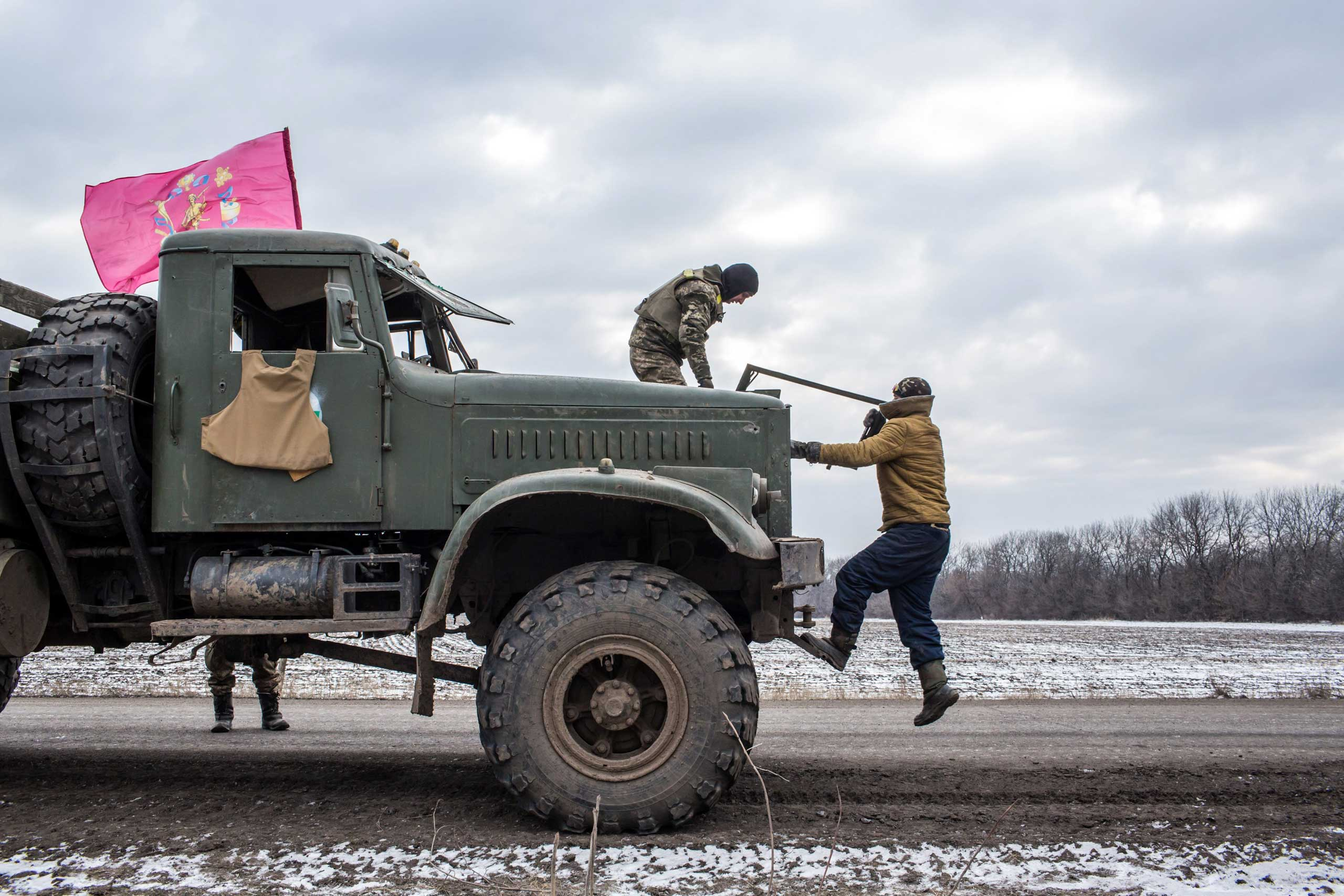 Ukrainian soldiers from a unit based in Zaporizhia repair the bullet-shattered windshield of a truck after taking fire during their withdrawal from Debaltseve the previous day on Feb. 19, 2015 in Artemivsk.