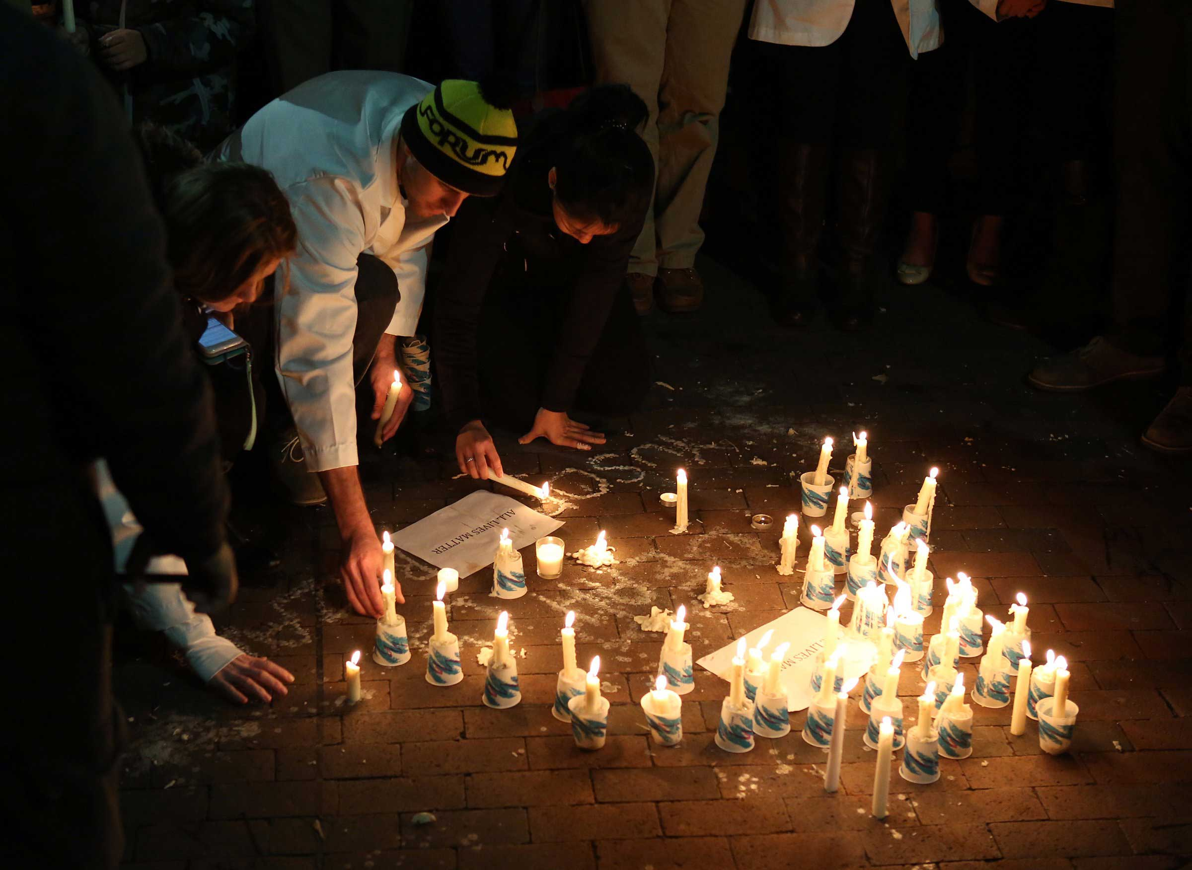 People light candles during a vigil on the campus of the University of North Carolina, for three Muslim students who were murdered, in Chapel Hill, N.C. on Feb. 11, 2015.