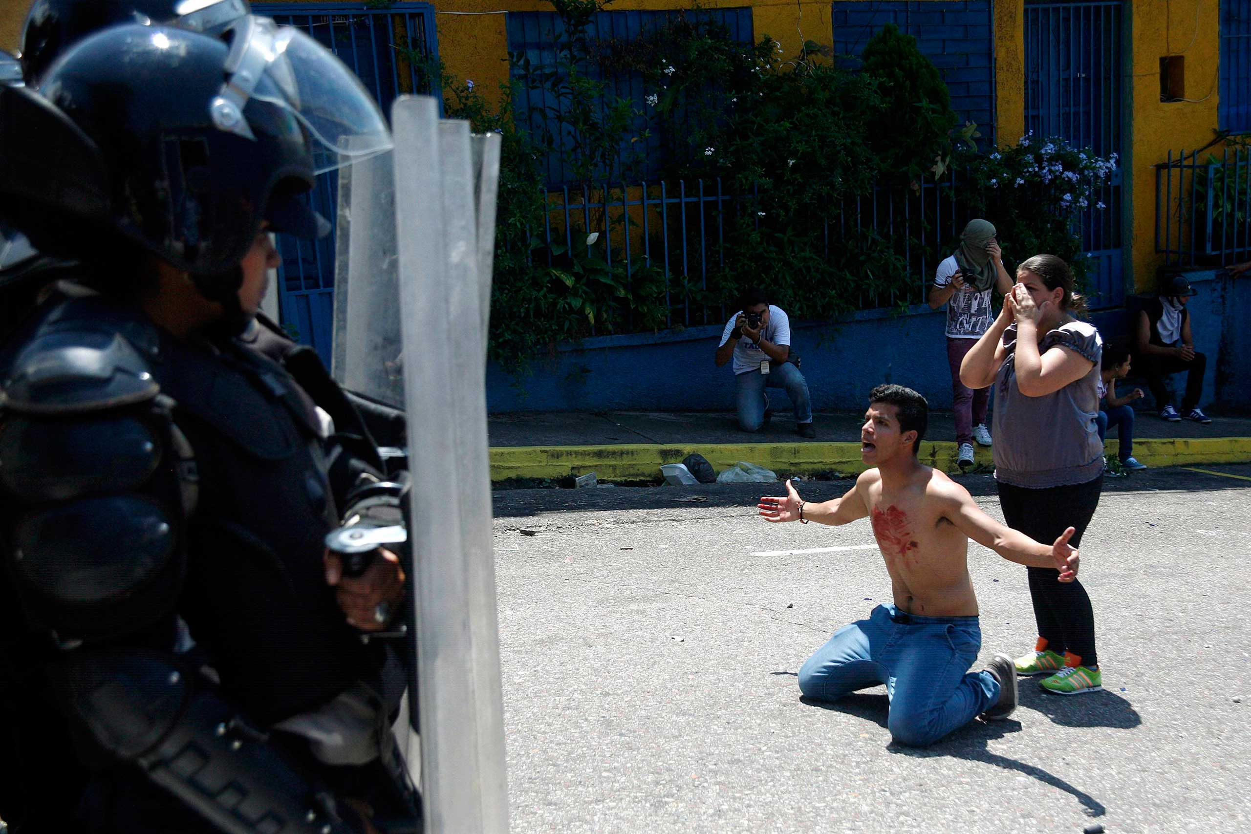 A boy with blood on his chest kneels in front of police after 14-year-old student Kluiver Roa died during a protest in San Cristobal, Venezuela, Feb. 24, 2015.