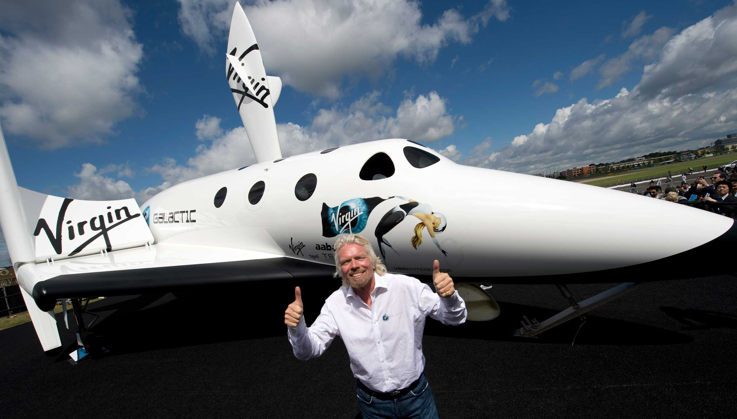 British billionaire Richard Branson poses in front of a model of the Virgin Galactic.
