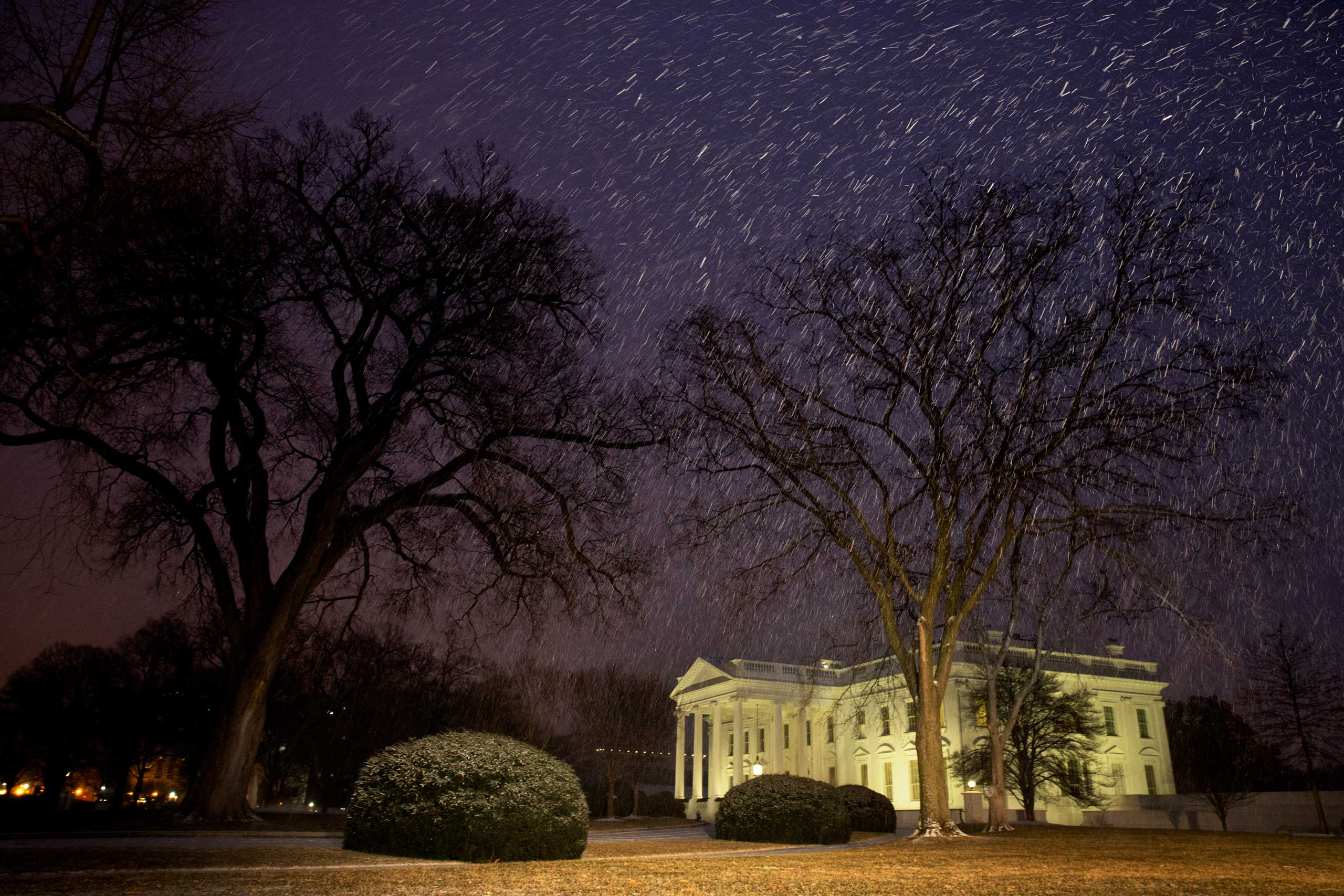 Snow falls at dusk by the White House in Washington on  Feb. 16, 2015,