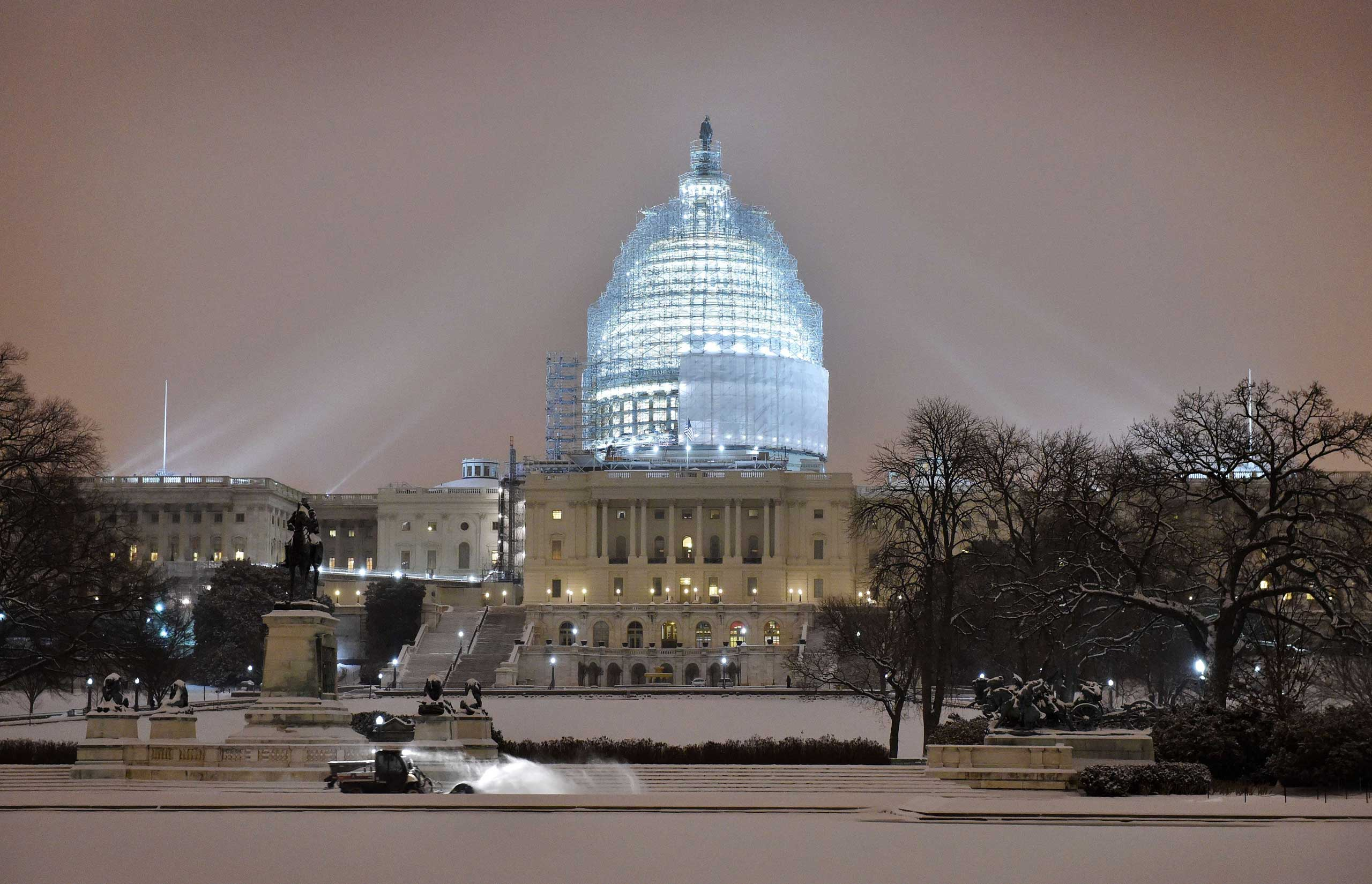 A snow-plough cleans the snow in front of the US Capitol building in Washington on Feb. 16, 2015.
