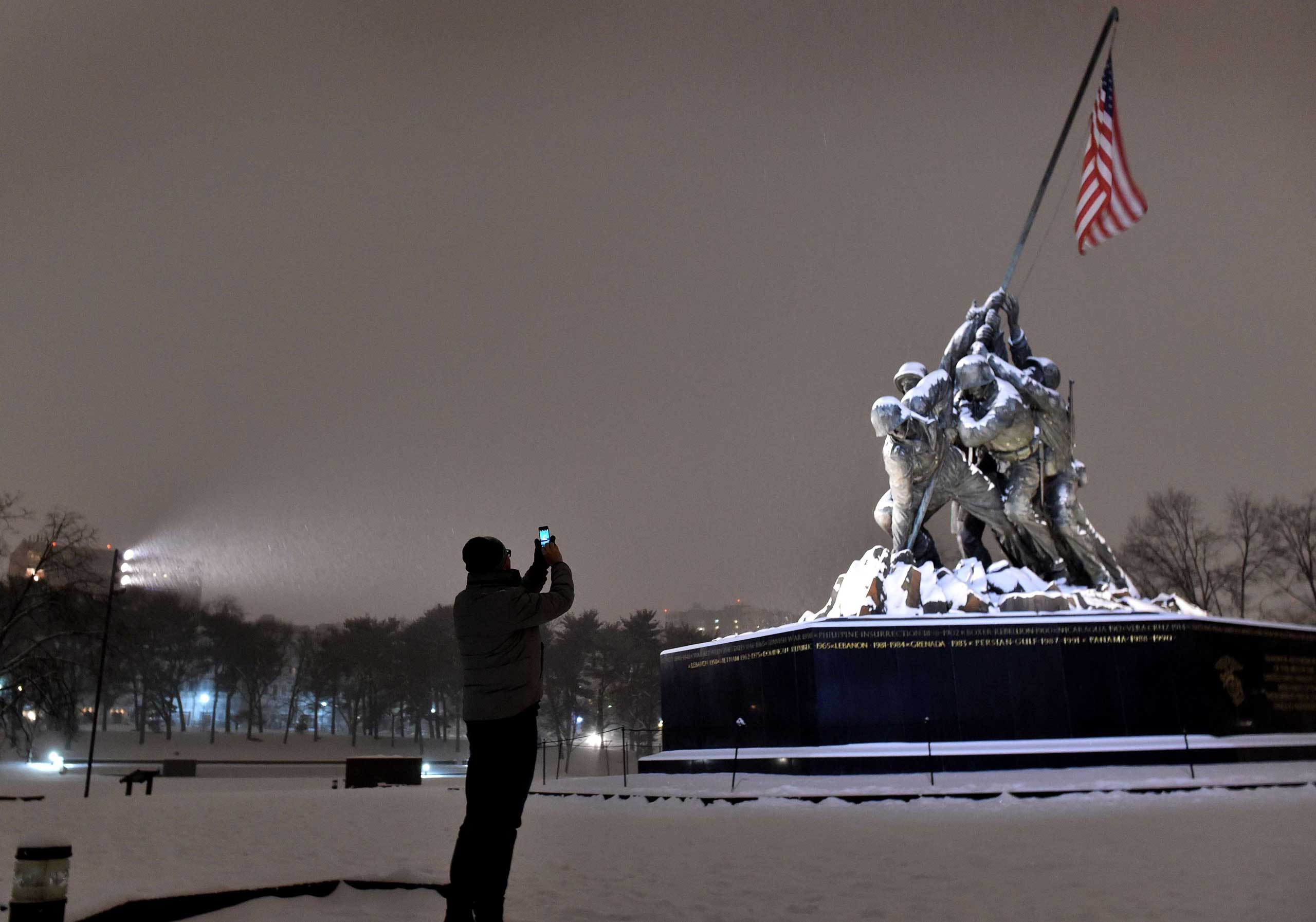 A man takes a photo of the snow covered Iwo Jima memorial in Washington on Feb. 16, 2015.