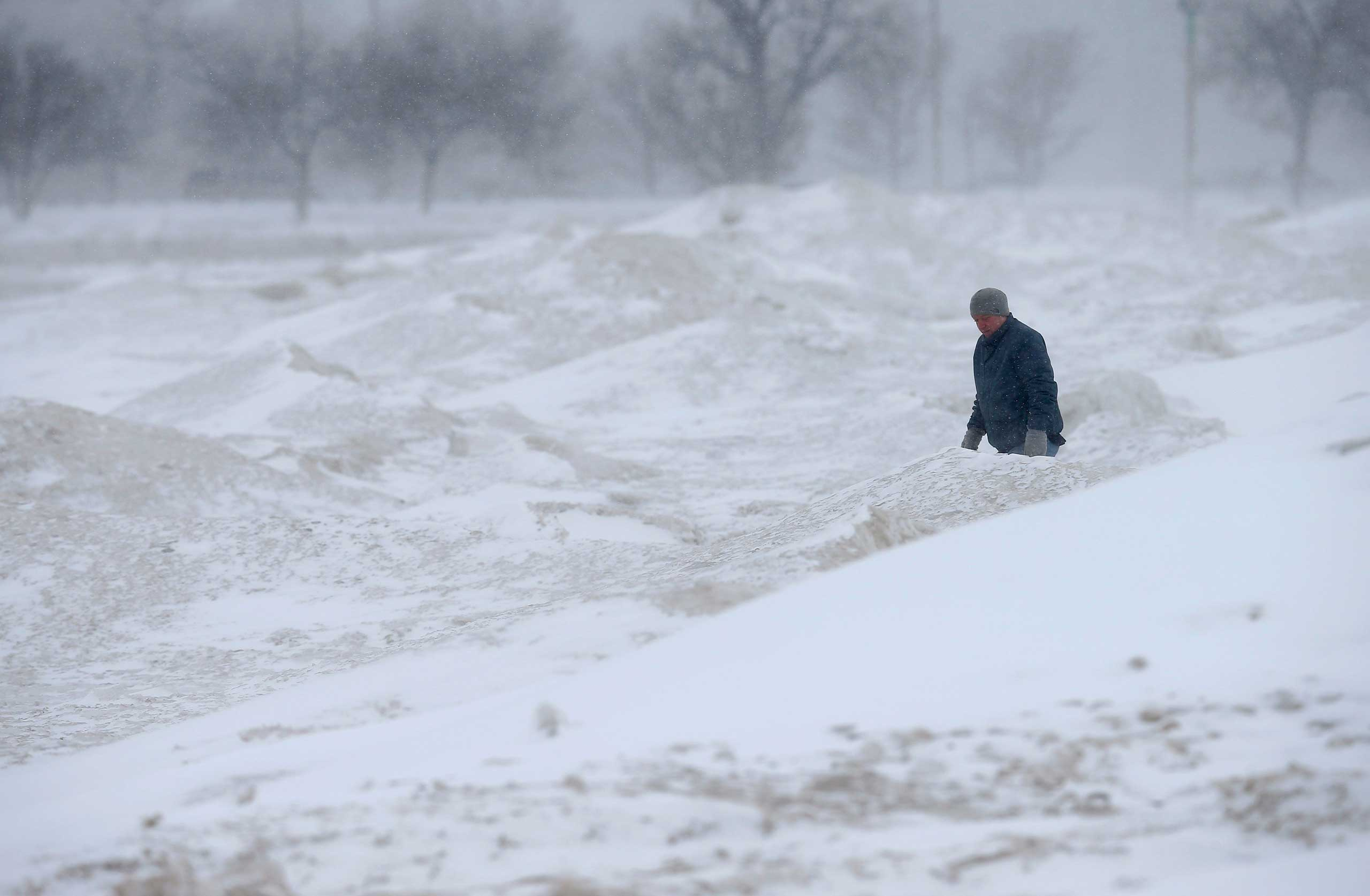 A man braces himself against the wind as he walks along mounds of snow and ice on North Avenue beach at Lake Michigan in Chicago on Feb. 26, 2015.