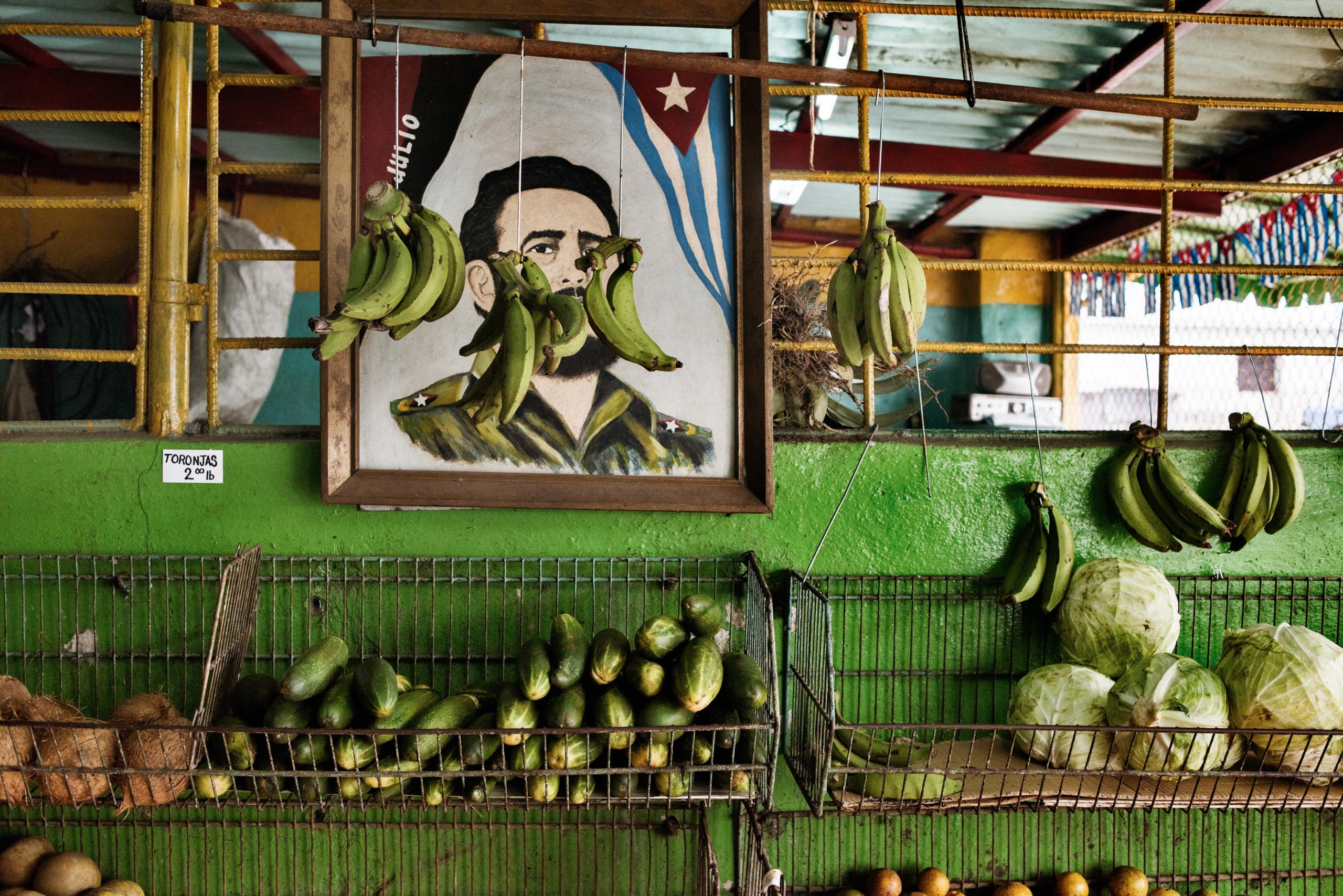 December 2014. In a state run market,  a portrait of Fidel Castro is seen among fruit and vegetables. Because of limited food supply, Cubans depend on monthly rations for basic staples like rice and beans.