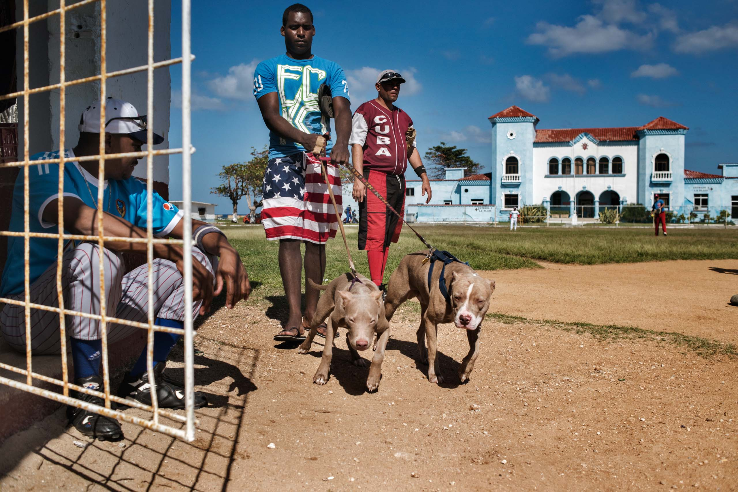 January, 2015. A young Cuban, wearing shorts decorated with the American flag, walks his dogs past a softball field in the Jaimanitas neighborhood of Havana.