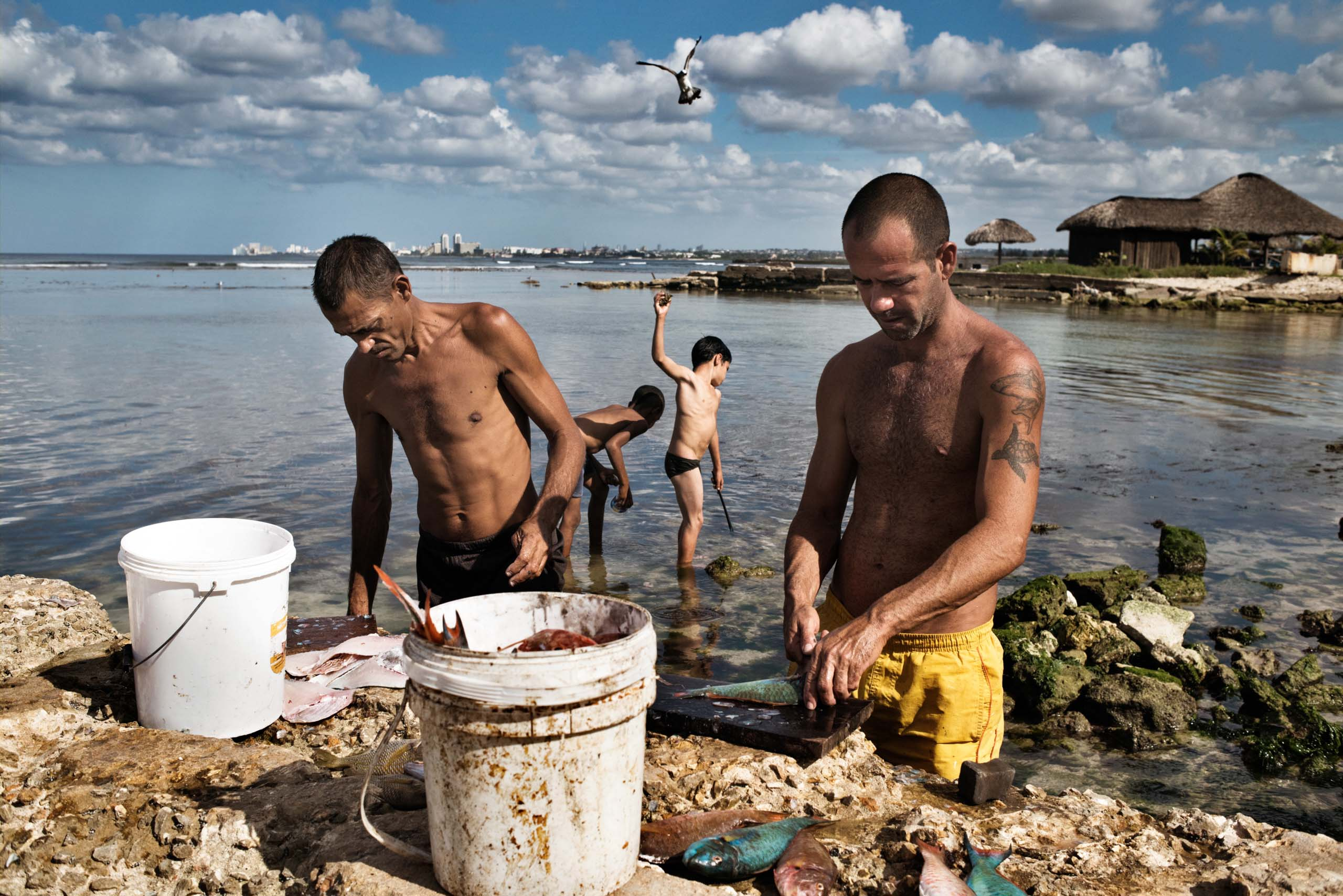 January 2015. Men clean fish, while children play by the shore, in the Jaimanitas neighborhood of Havana.