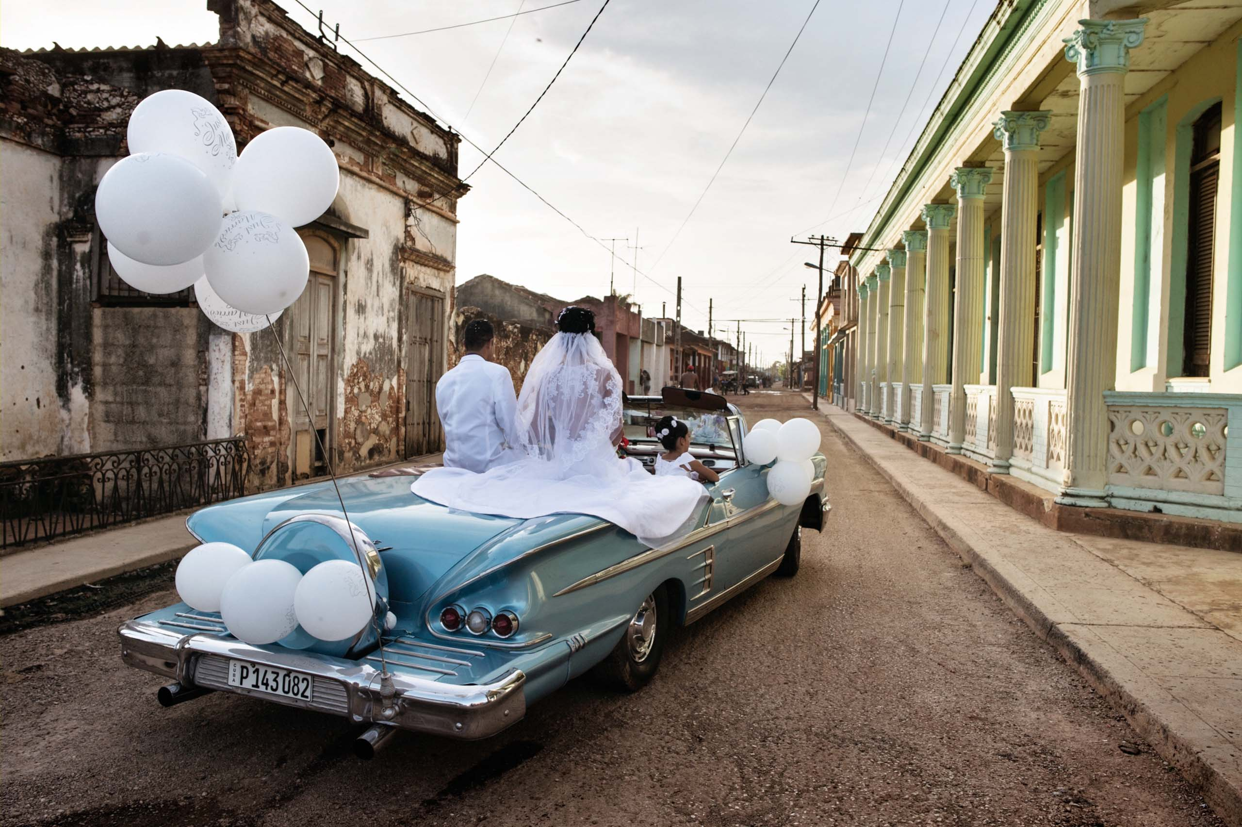 January 2015. Newlyweds ride in a vintage American car through the streets of Guira de Melena. In this prosperous area outside Havana, weddings can cost as much as $20,000.