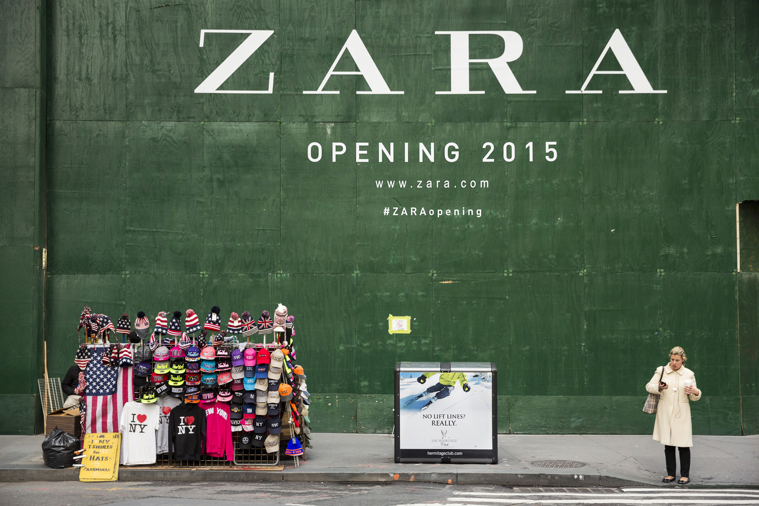 A woman checks her phone next to the construction site of a new Zara store in downtown Manhattan, New York, Dec 17, 2014.