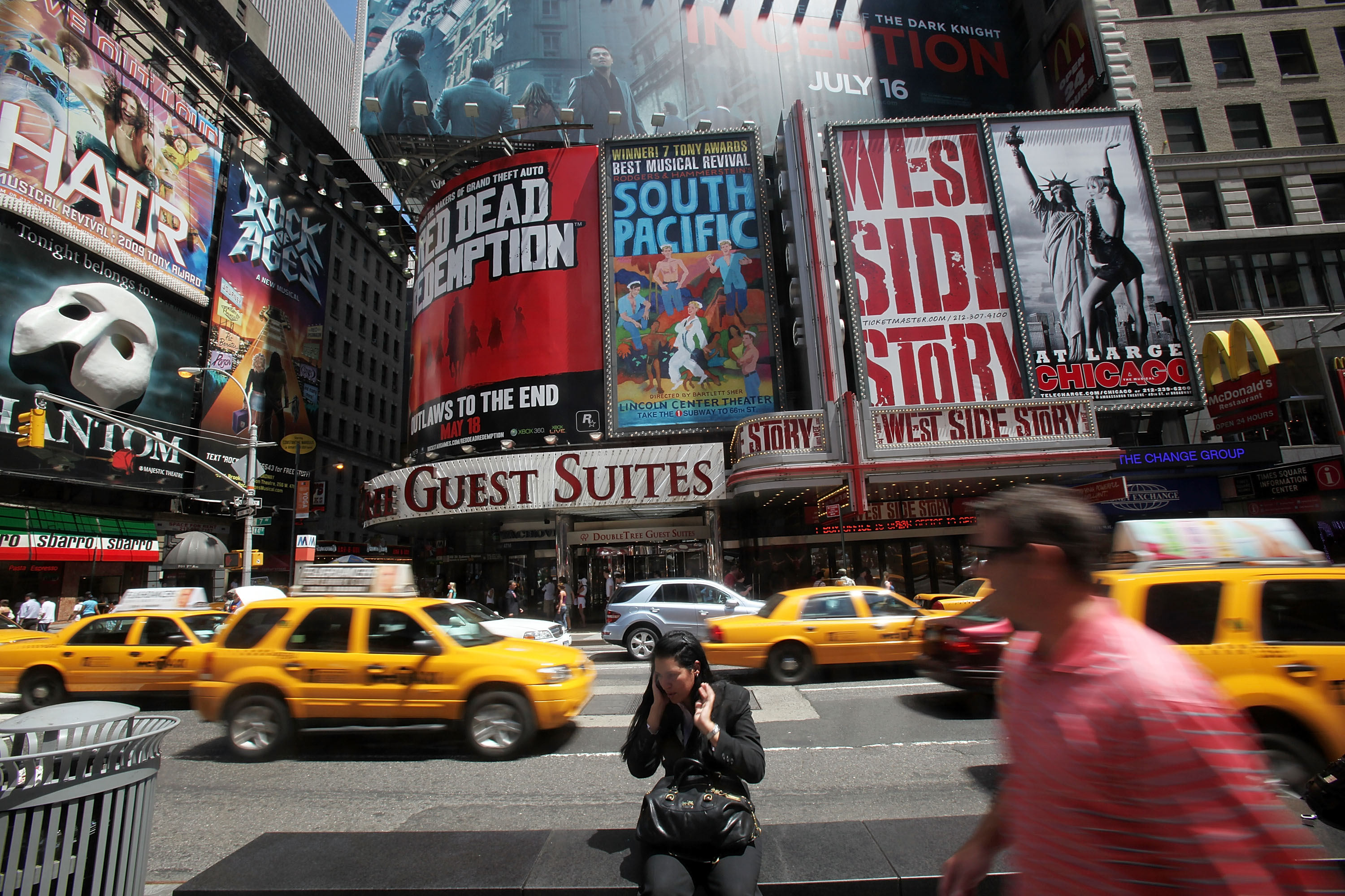 Taxis pass Broadway theater  billboards in Times Square in New York City.