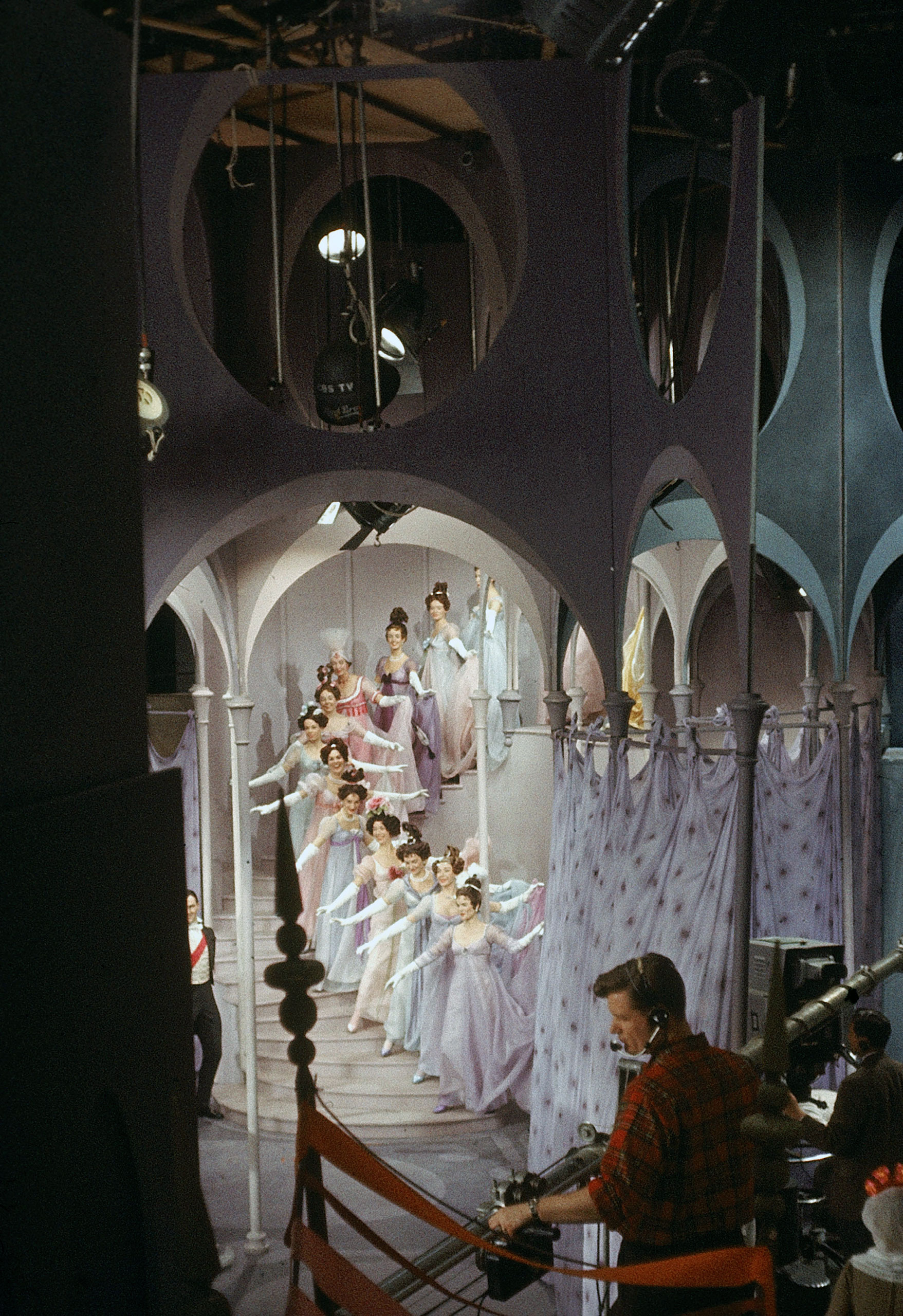 <b>Caption from LIFE.</b> On royal stairway dancers wait for grand waltz while a technician listens for cue to start.