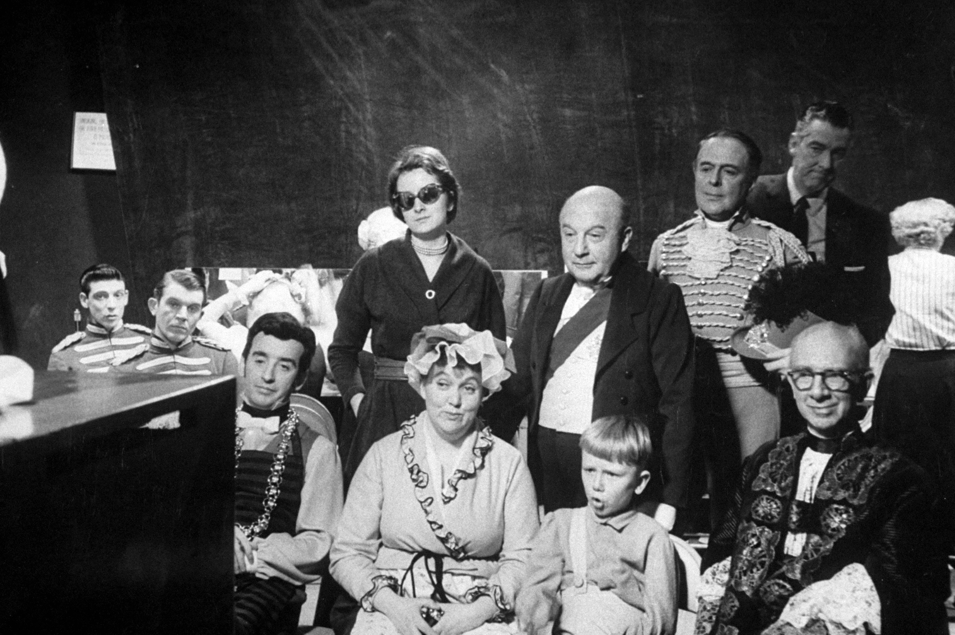 <b>Caption from LIFE.</b> Watching the star, members of the cast gather around a monitor television set, some of their faces beaming satisfaction, others still nervous lest something go wrong in the last few moments of the show. They are listening to Julie Andrews sing <i>A Lovely Night,</i> a musical recapitulation of the royal ball.