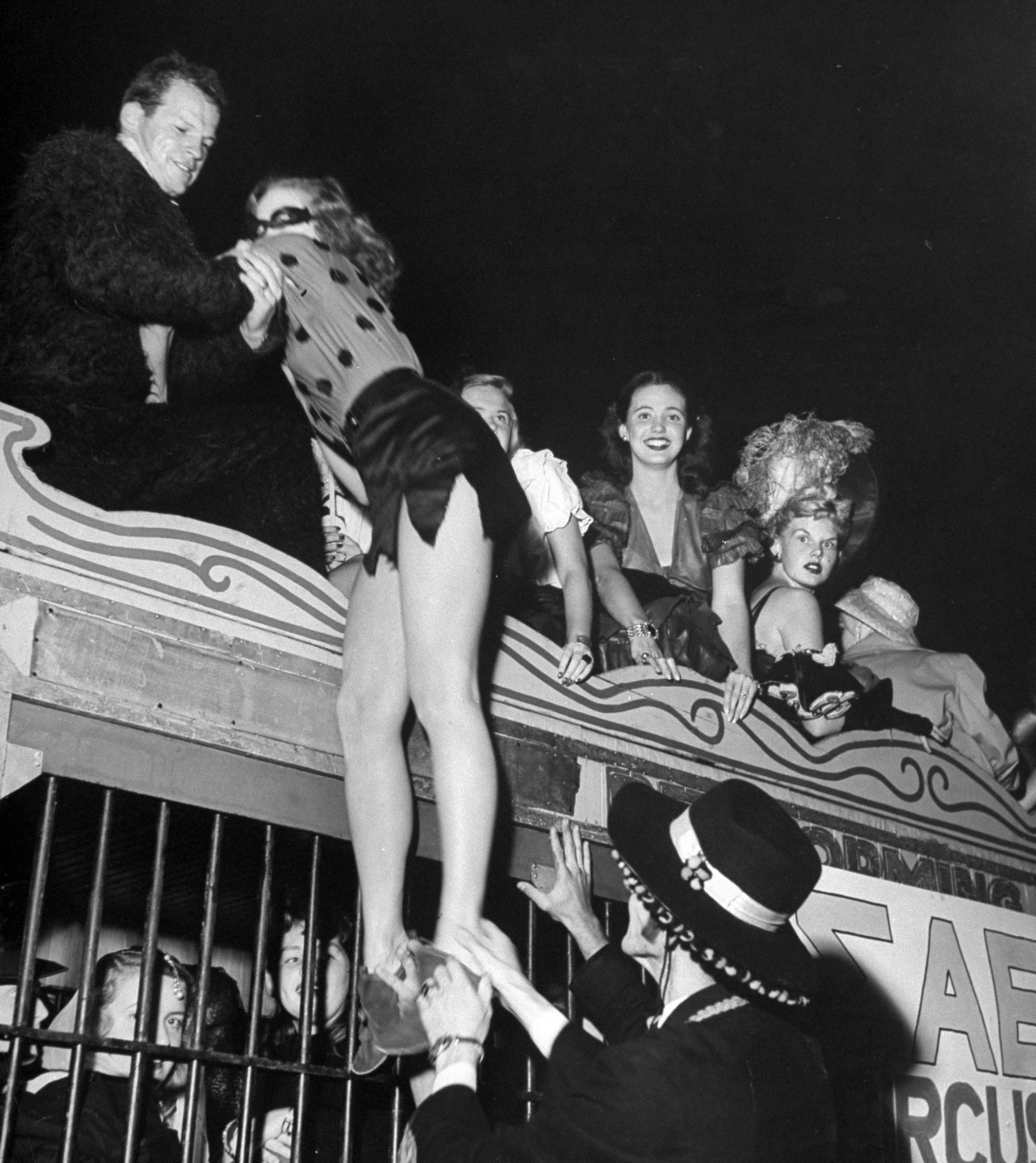 <b>Caption from LIFE.</b> A long-legged coed gets hoisted atop a circus wagon which will take her to the Sigma Alpha Epsilon circus masquerade party at U.C.L.A. The inside of the wagon, which normally is used for lions by a local circus, was already full of other guests. Halfway to the party the wagon broke down and the girls and their hosts continued on foot.