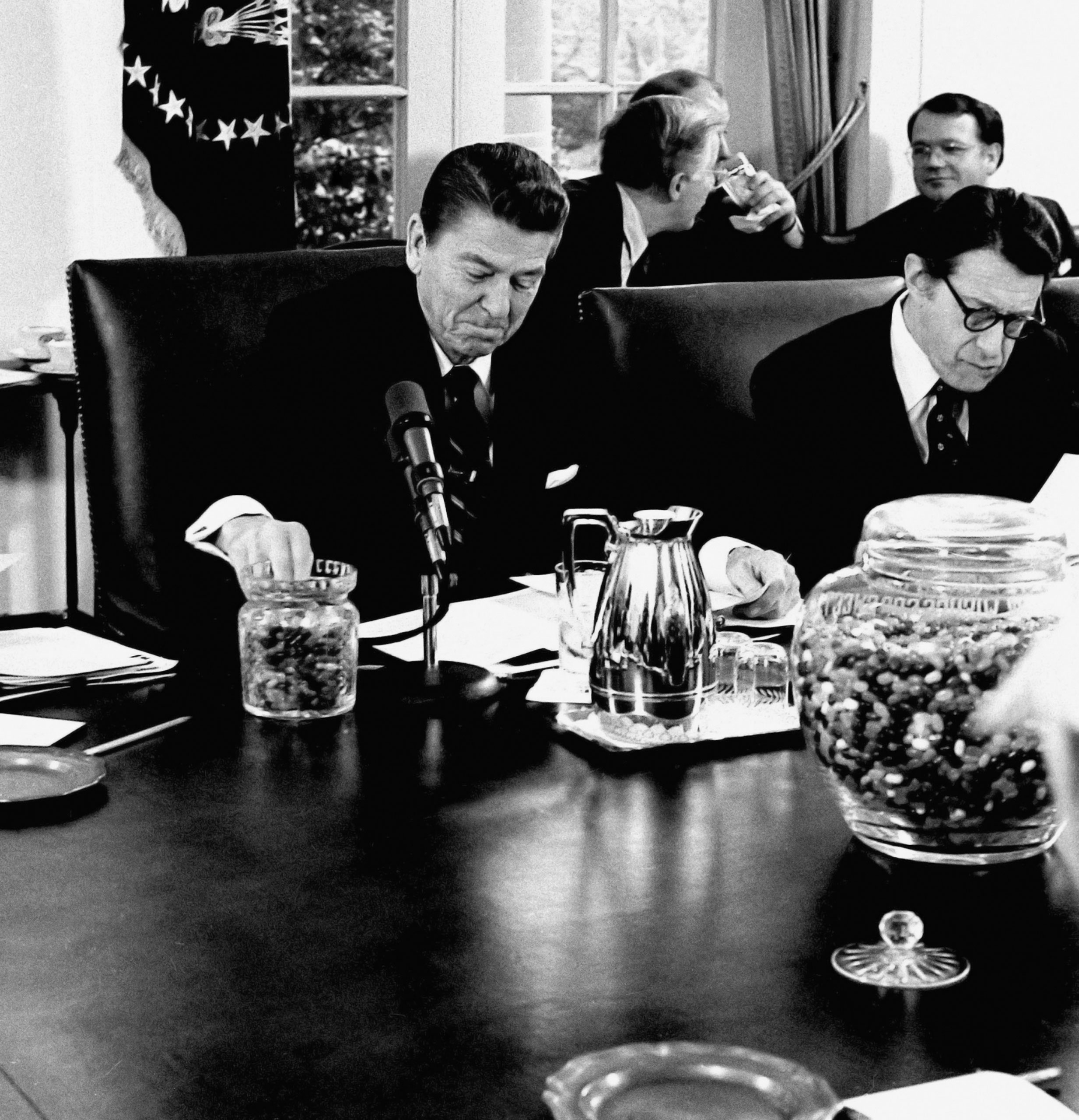 Ronald Reagan eating jelly beans during a meeting.