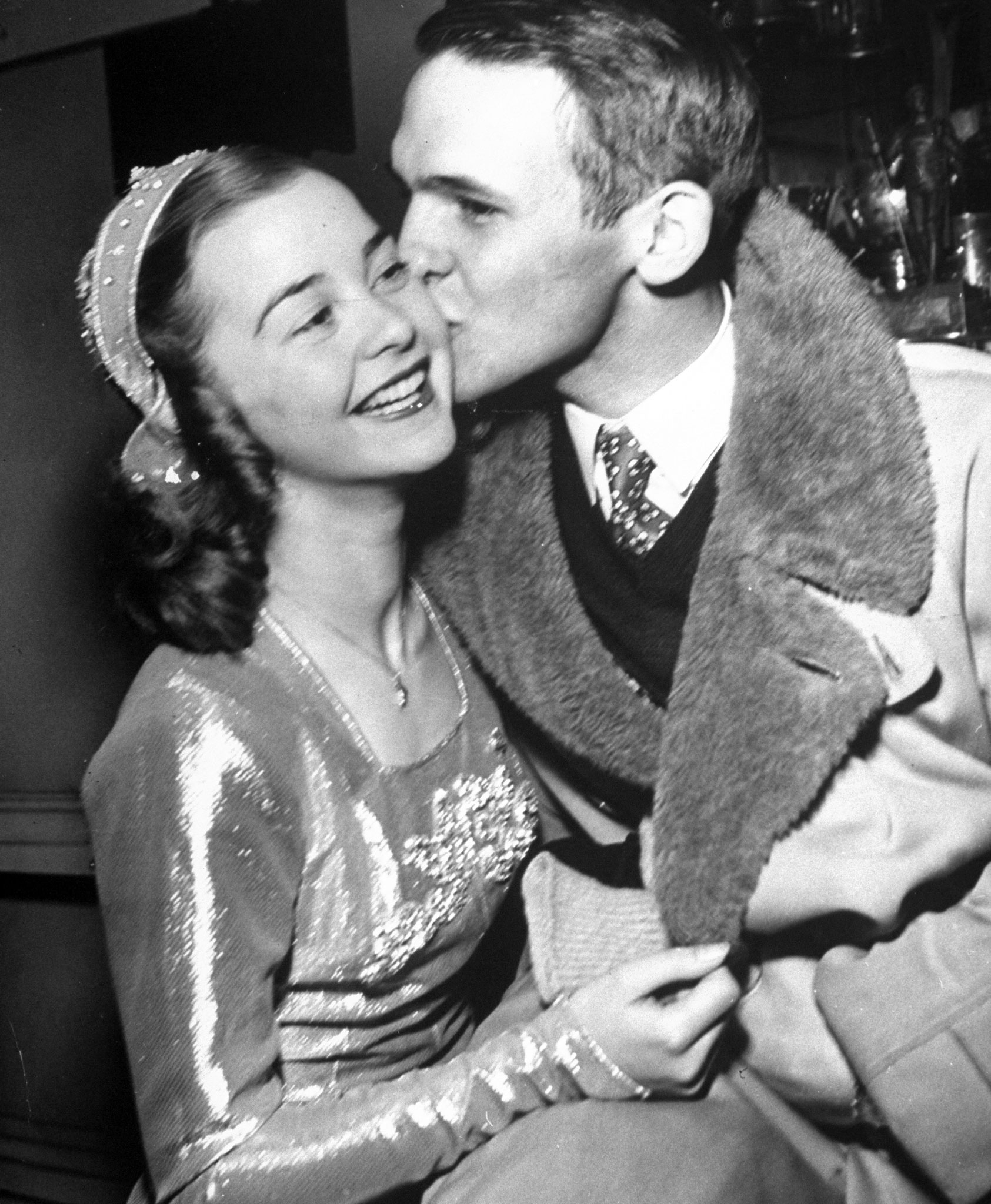 <b>Caption from LIFE.</b> Barbara gets kissed by Richard Button after her victory. Good-luck piece is still around her neck.