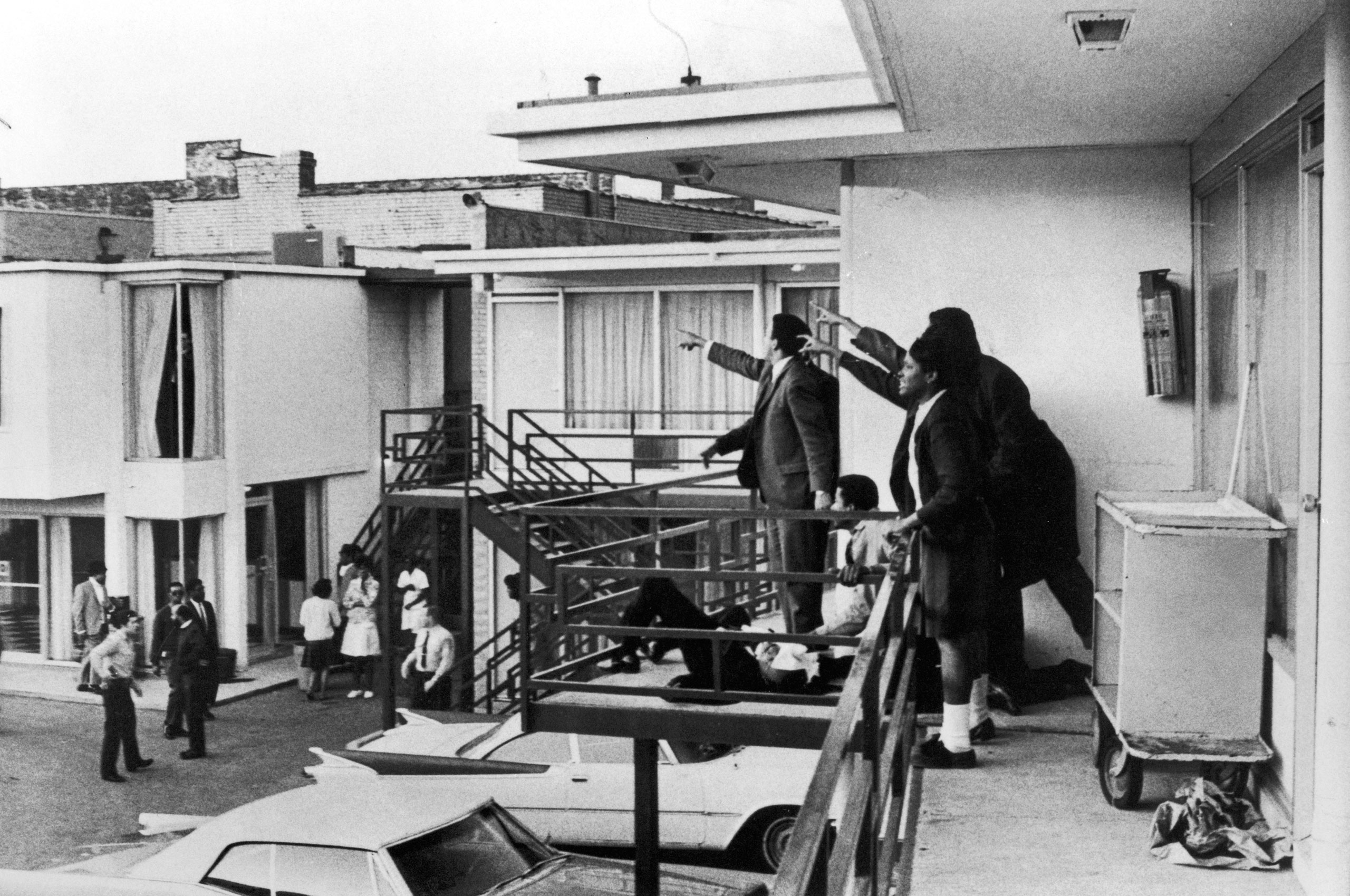 Civil rights leader Andrew Young (L) and others standing on balcony of Lorraine motel pointing in direction of assailant after assassination of civil rights ldr. Dr. Martin Luther King, Jr., who is lying at their feet.