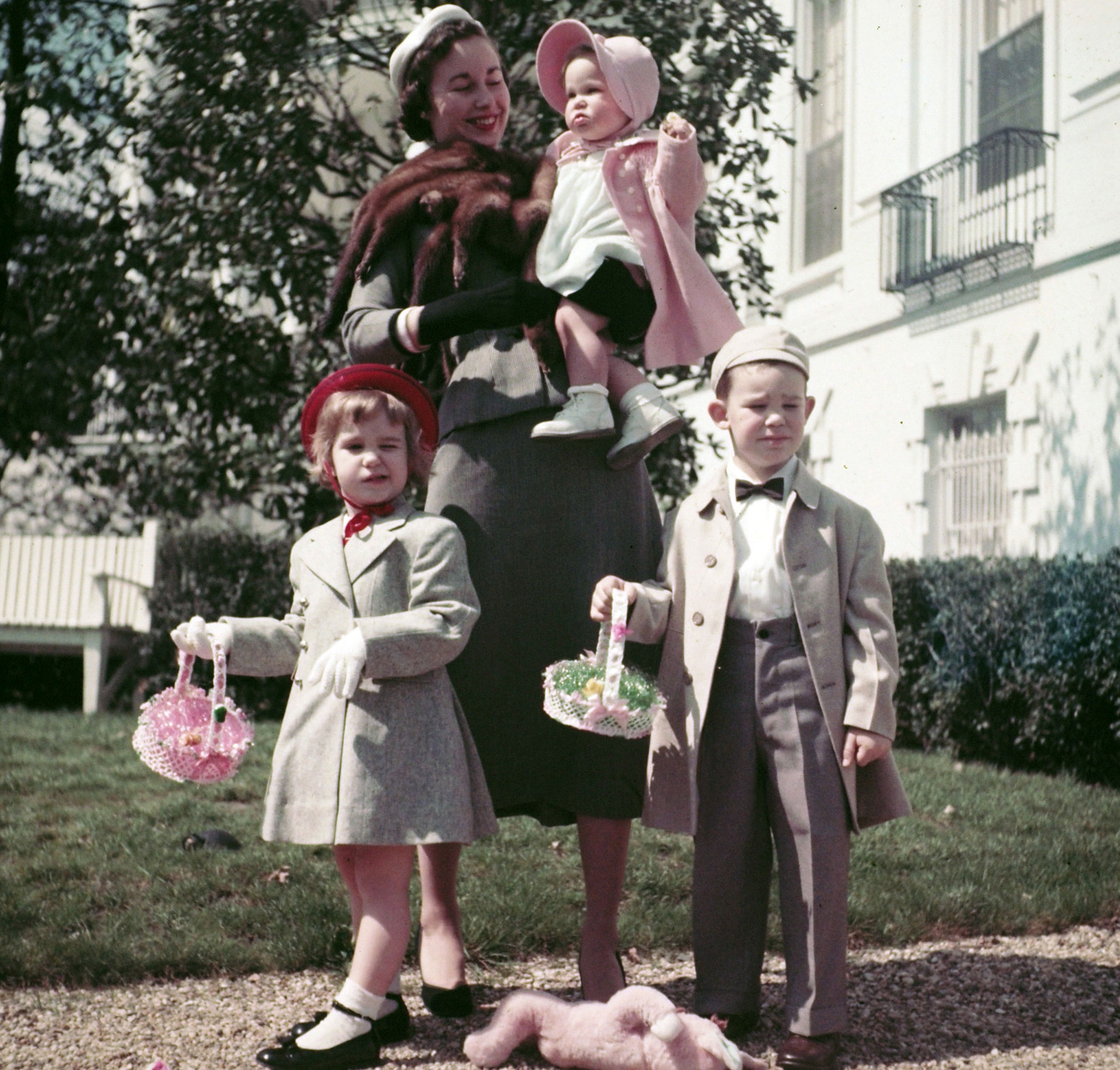 """<b>Caption from LIFE.</b> In spring clothes, Eisenhower's grandchildren display their finery. Baby Susan, held by her mother Barbara, wears springlike pink. LIttle Barbara Anne, cocking a wink, has some """"big girl"""" gloves and a red-ribboned hat. David has an Eton cap and the snappy bow tie currently fancied by five-year-old pace-setters."""
