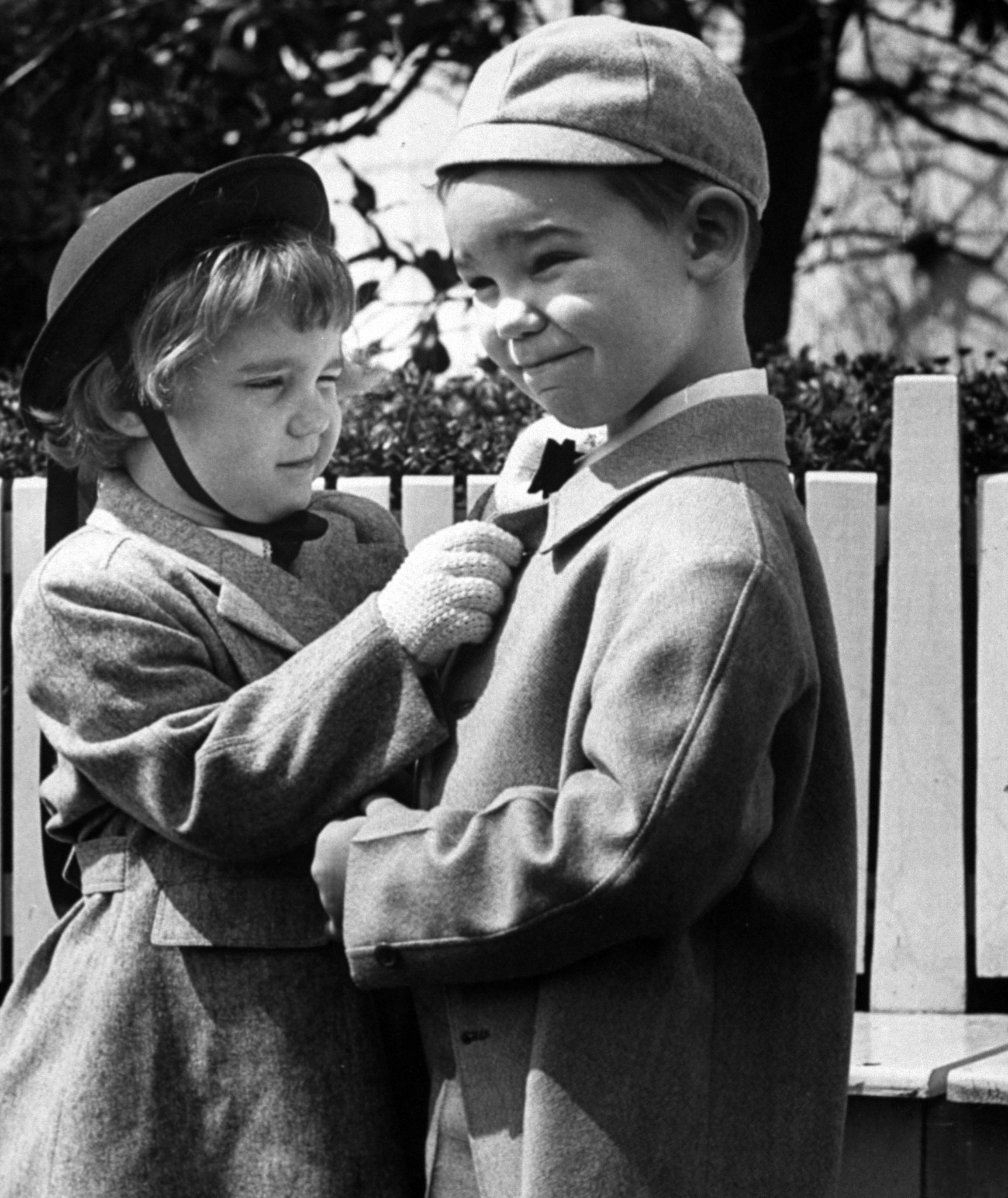 <b>Caption from LIFE.</b> Sisterly touch is given David Eisenhower's collar by his sister Barbara. Their little sister Susan who is only 1, was too young to attend the egg rolling.