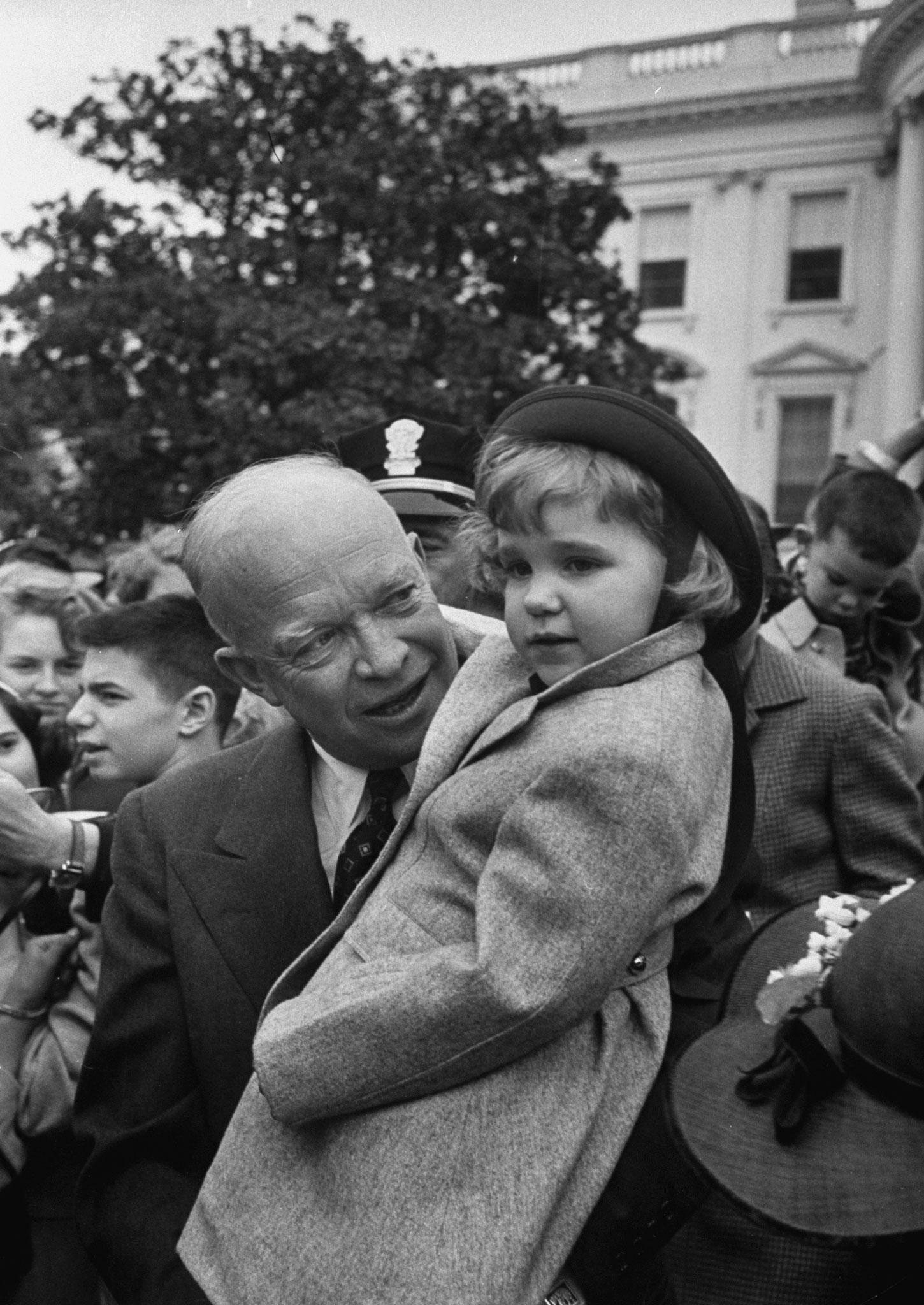 President Dwight D. Eisenhower holding his granddaughter, during the White House Easter egg roll, April 1953.
